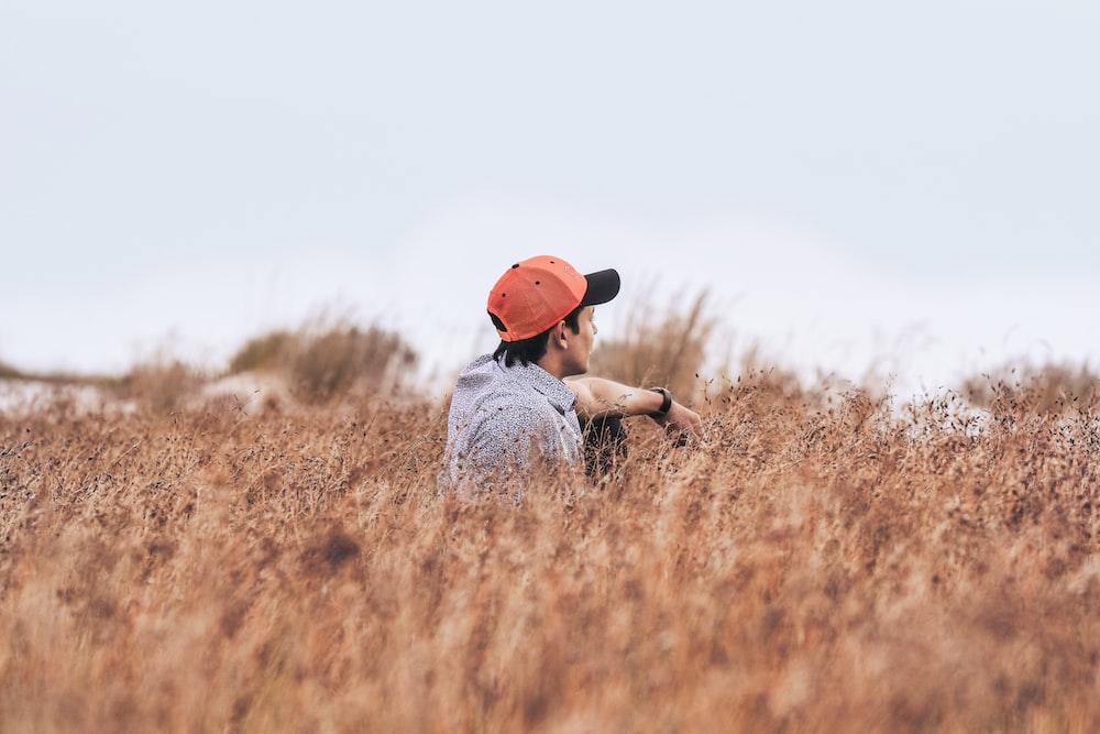 sitting man wearing red cap on brown flower field at daytime