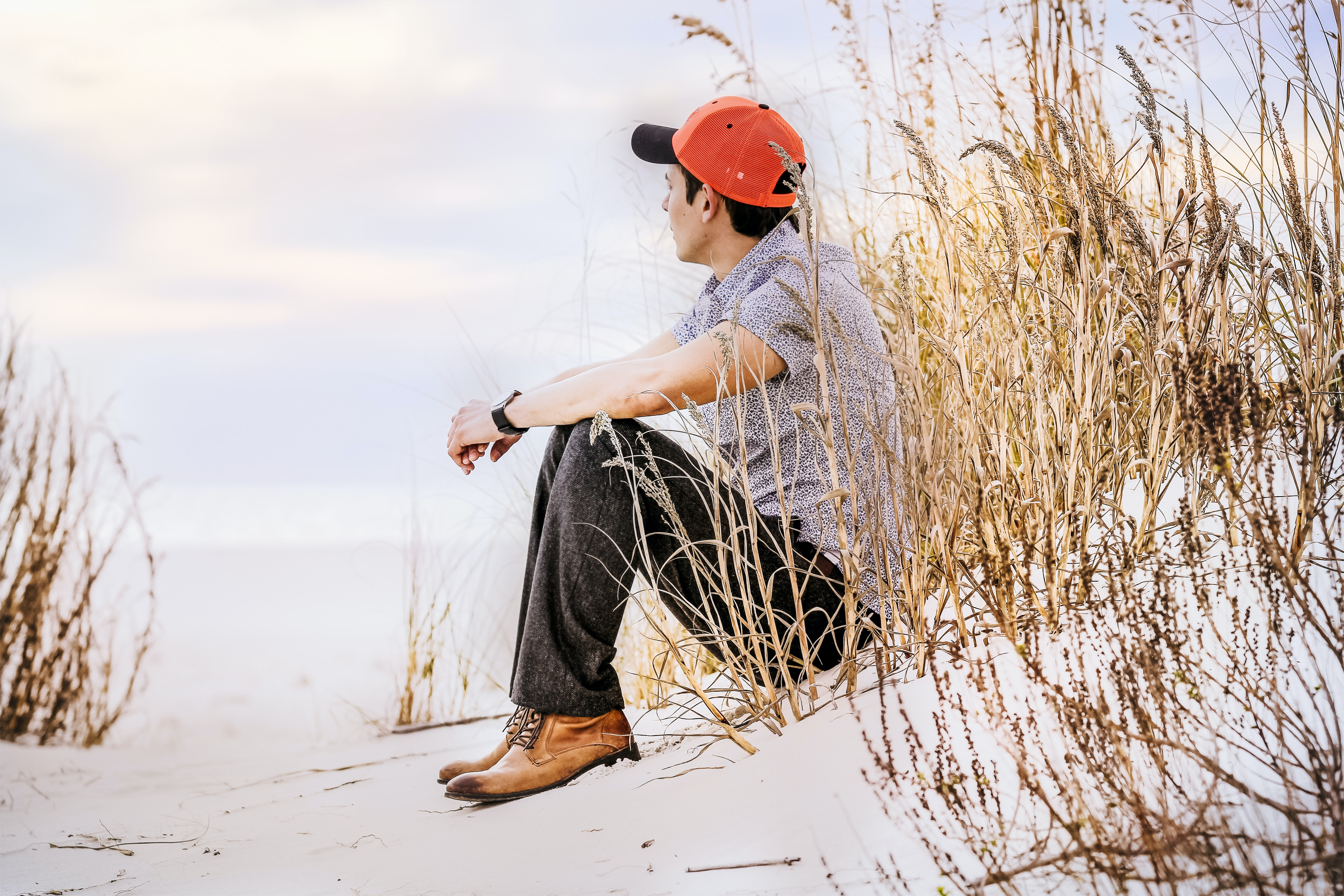 Man wearing a cap and a watch sitting down on sand