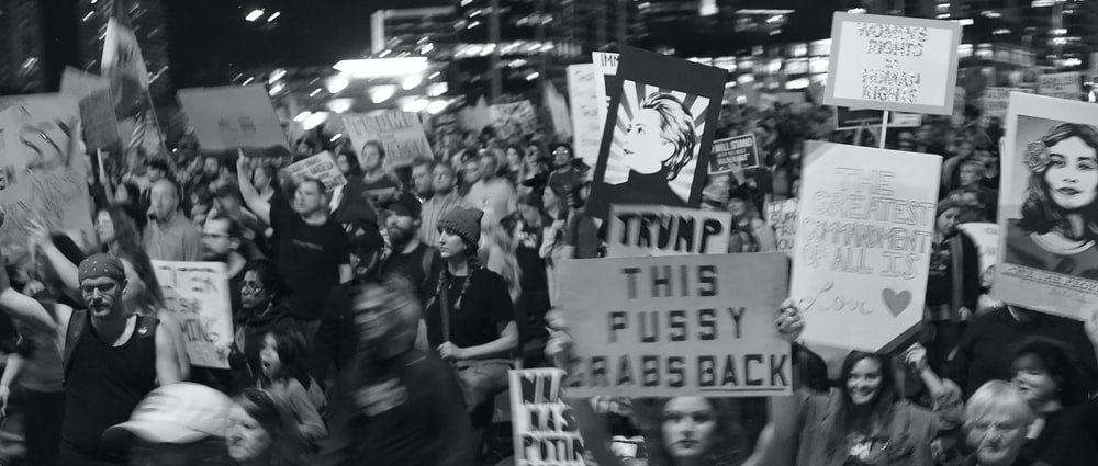 grayscale photo of people holding signages