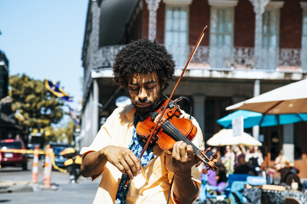 A man playing the violin or fiddle on the streets in New Orleans in the French Quarter