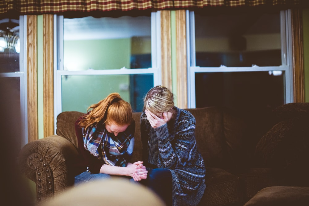 Two people in mourning or grieving on a couch in a living room