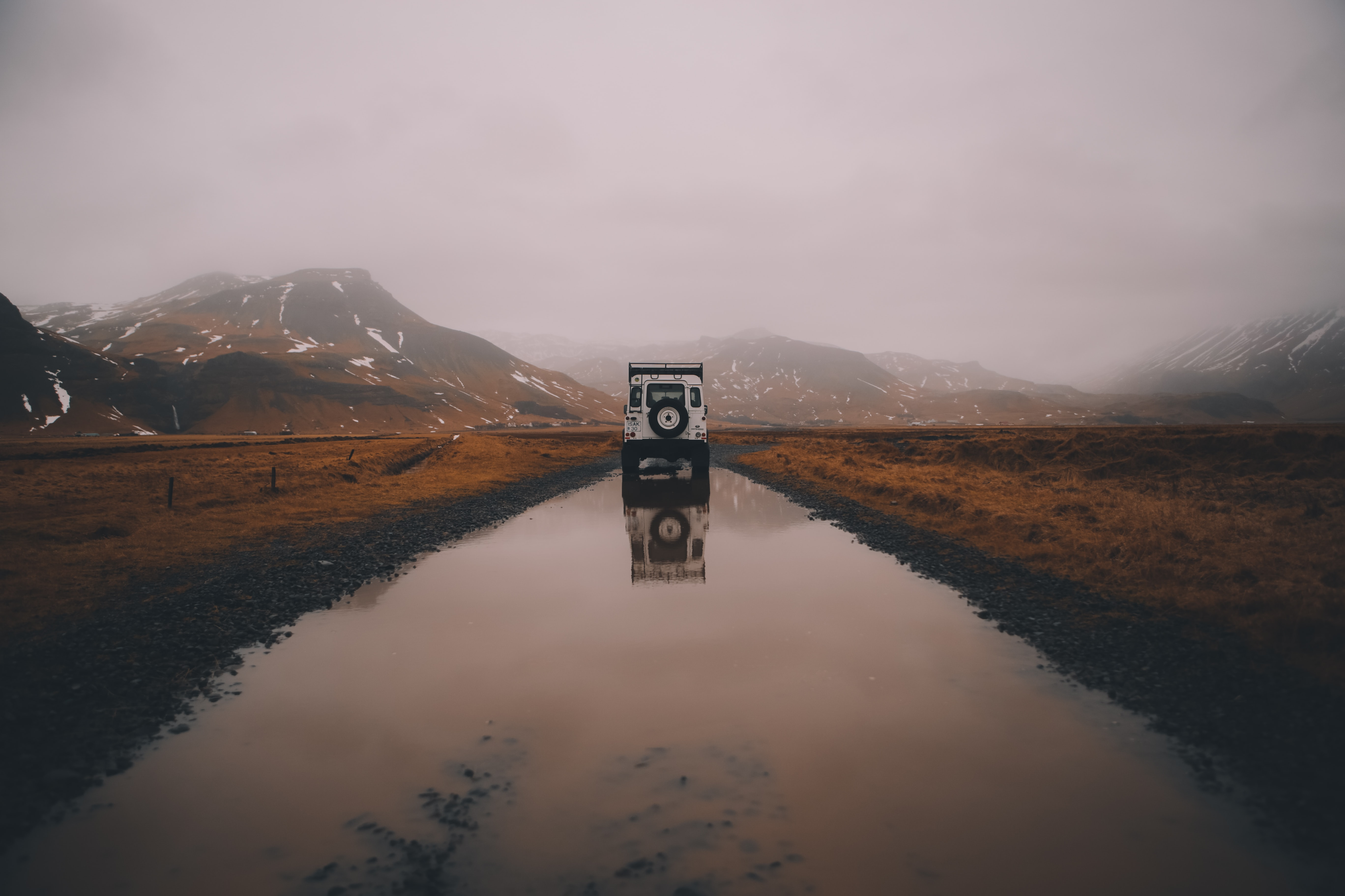 White offroad Landrover in a foggy Skógar region reflected in a puddle of water