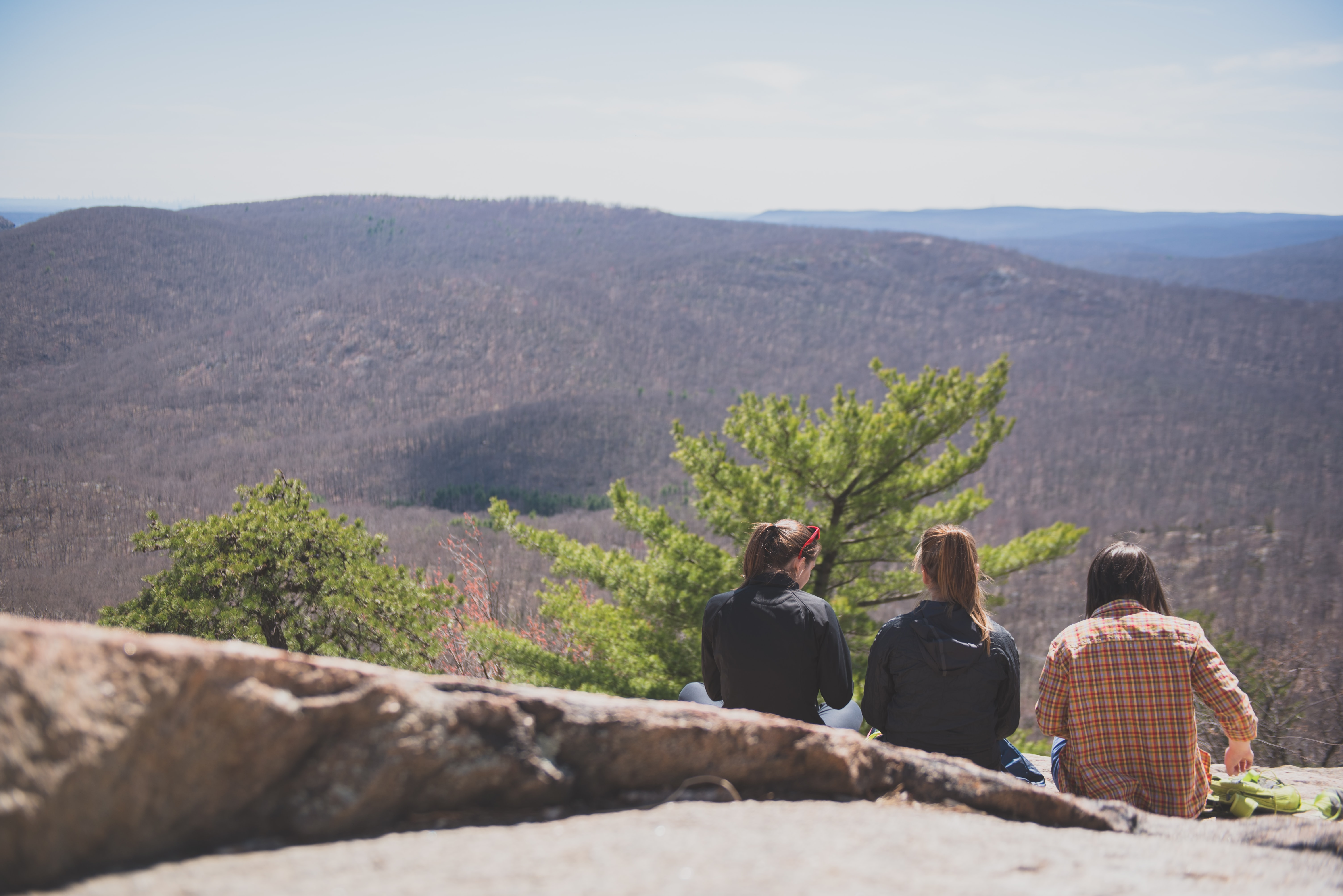 Three female friends sitting on a rock in Bear Mountain Park overlooking hills with leafless trees