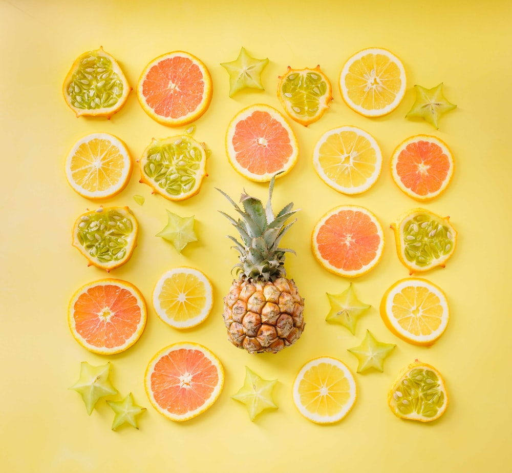 pineapple surrounded by citrus fruits