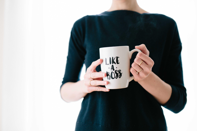 """A woman holding a white mug with a """"like a boss"""" print"""