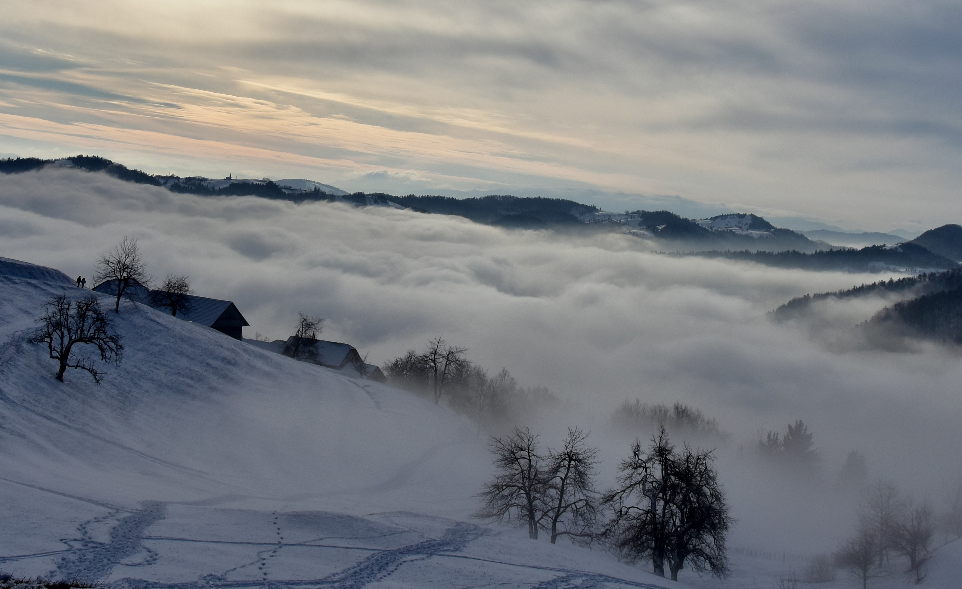 Rolling clouds cover winter cabins in a rural valley