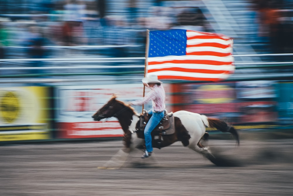 A person on a horse galloping in an arena holds the American flag