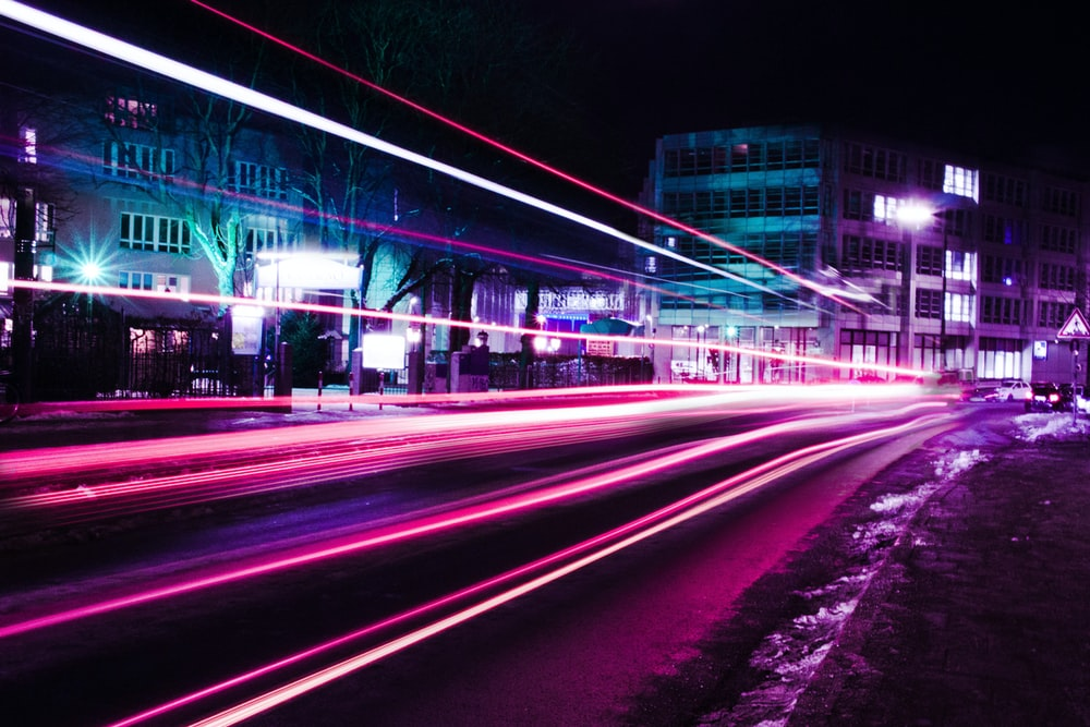 timelapse photography of pink vehicle lights near buildings