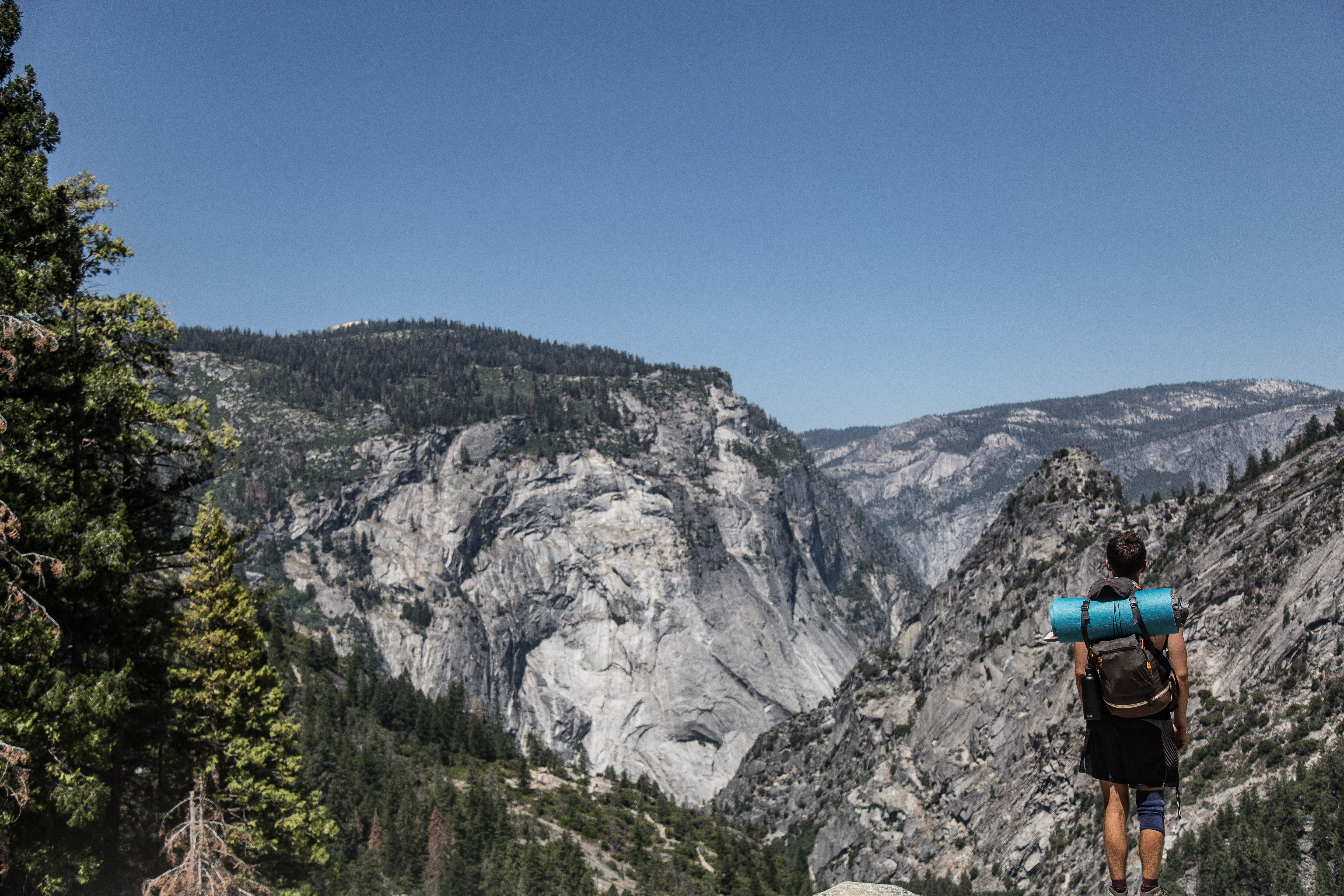 A male hiker with a backpack on a ledge in the Yosemite Valley