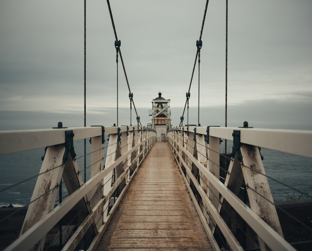 brown wooden lighthouse with bridge near seashore during daytime