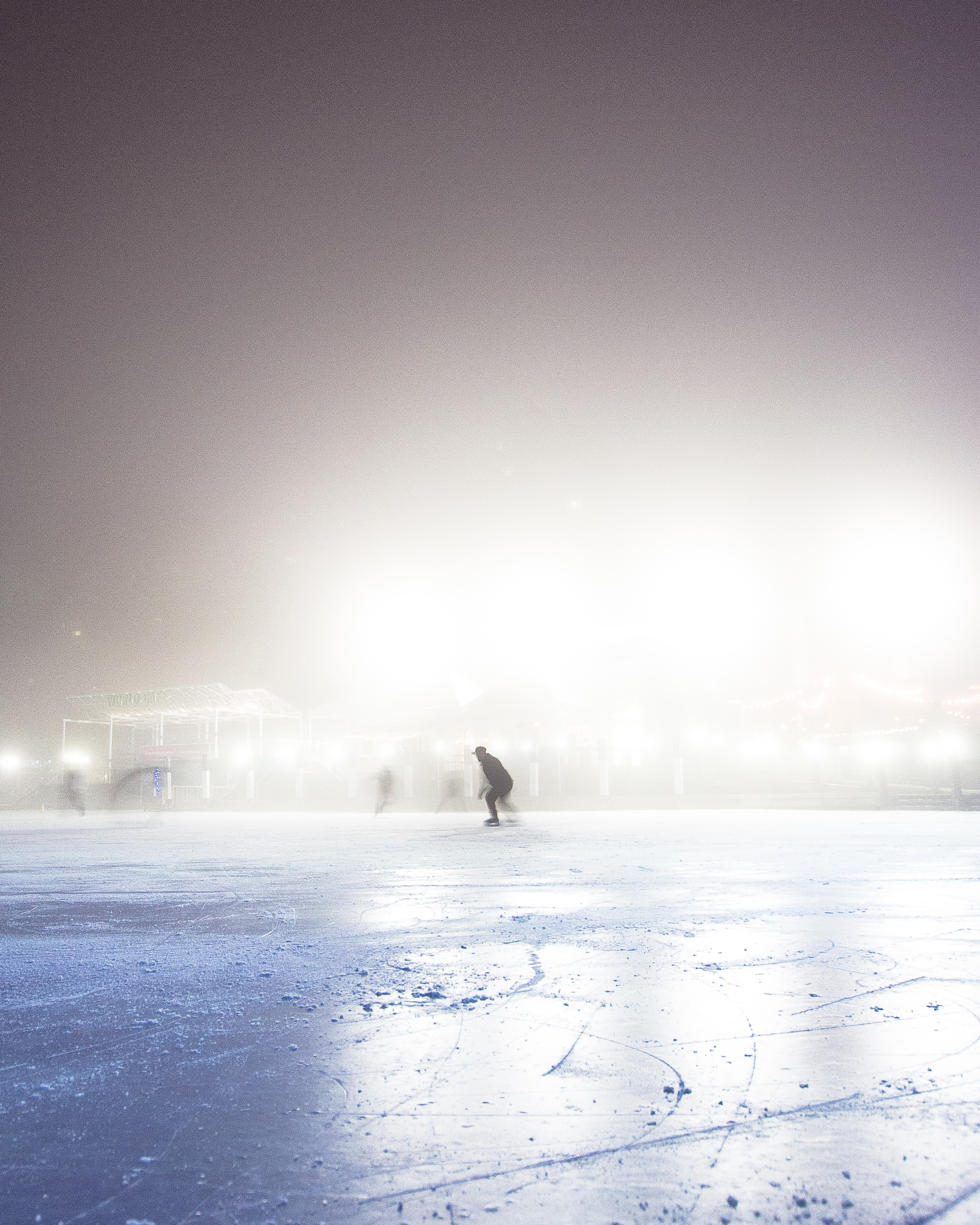 Silhouette of people skating on an ice rink on a misty winter night