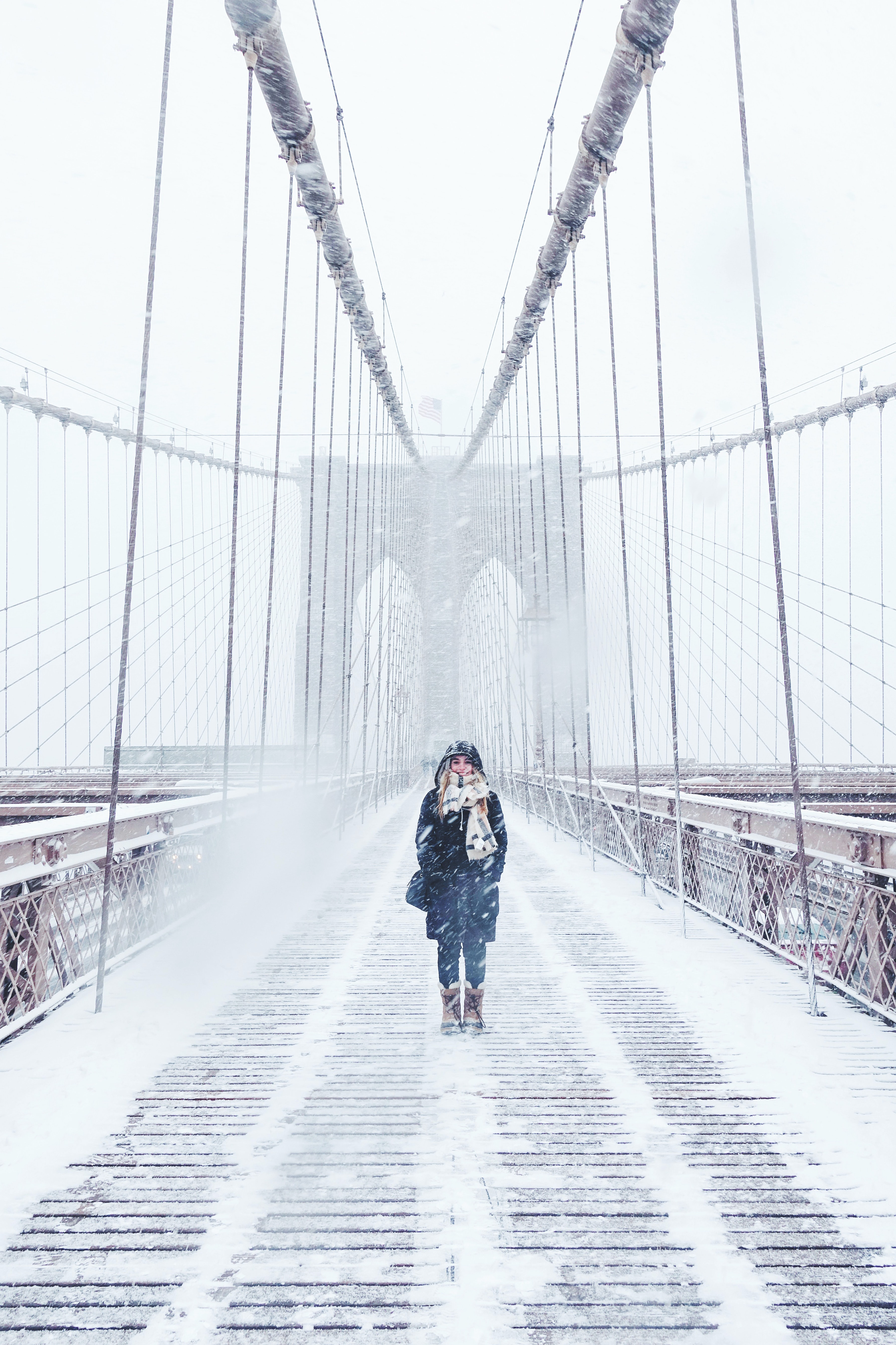 woman wearing black fur-lined coat standing on the bridge with snow during daytime photography