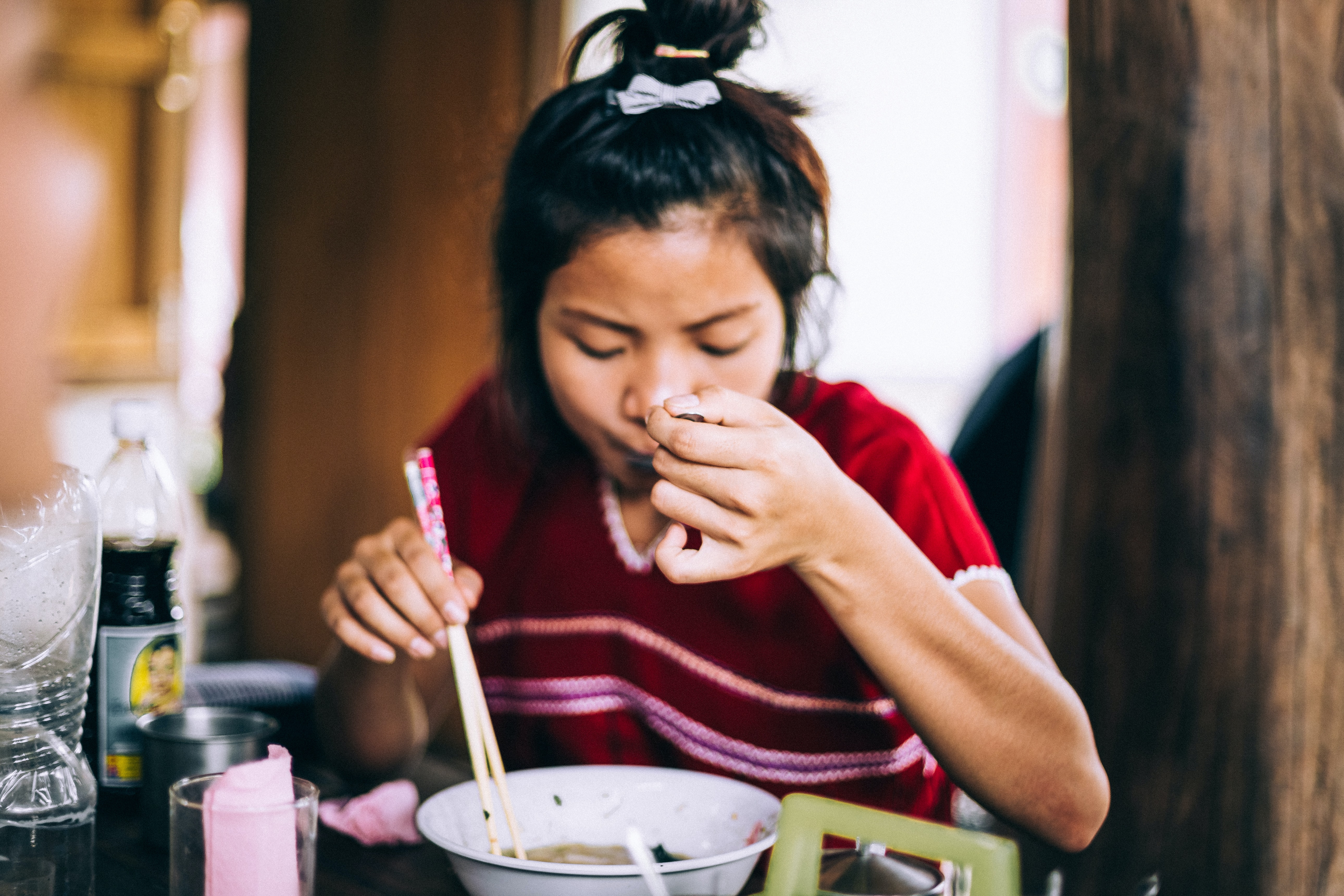 woman eating noodles while holding spoon and chopsticks