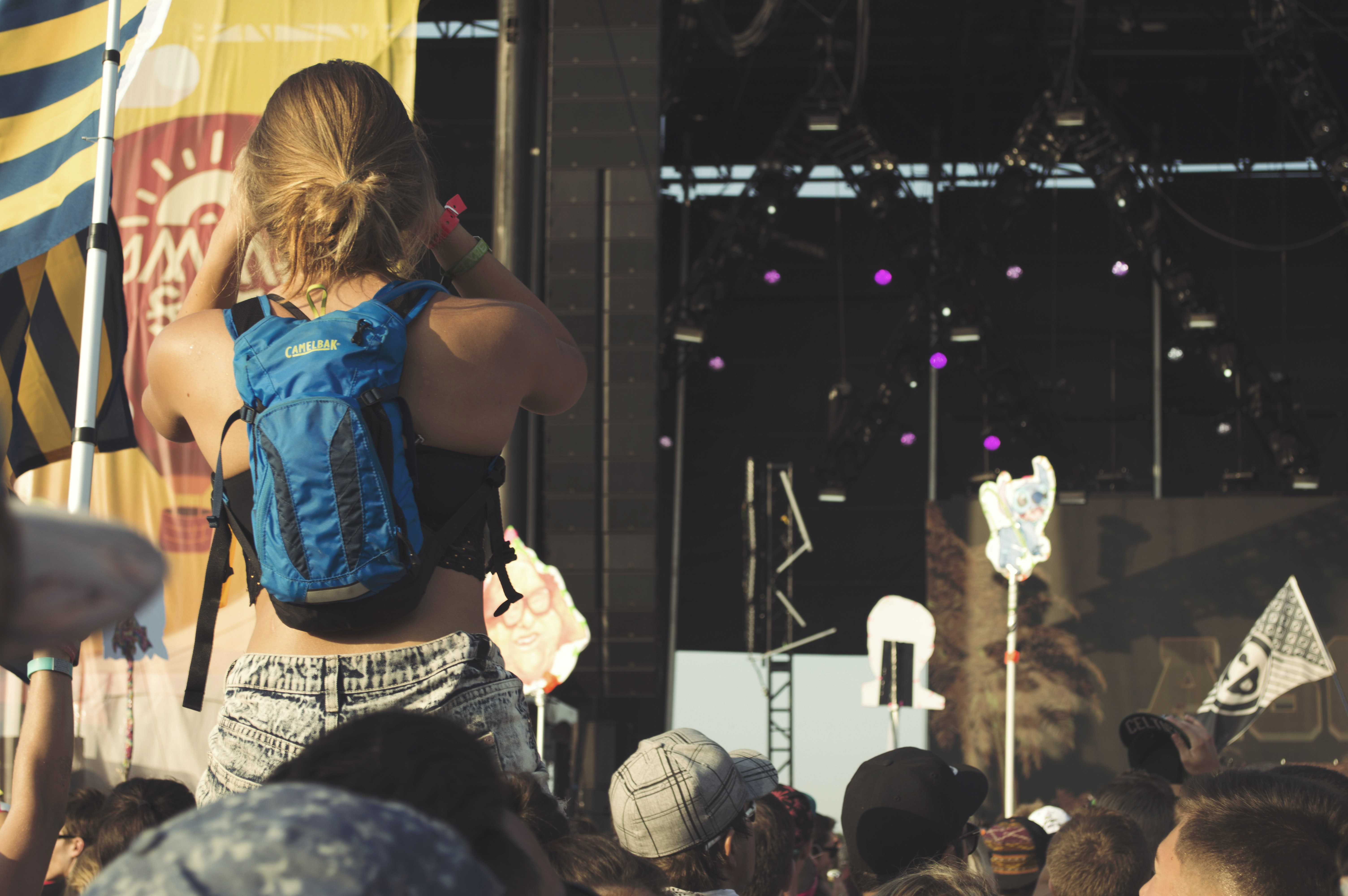 Woman sits on a friend's shoulders before an outdoor concert at a music festival