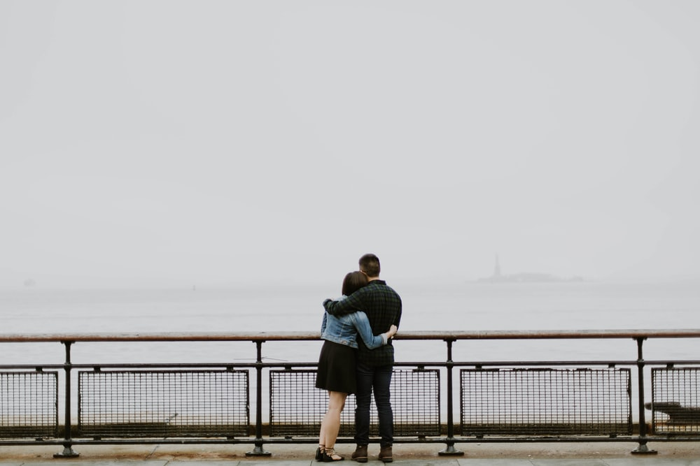couple standing in front of fence near body of water