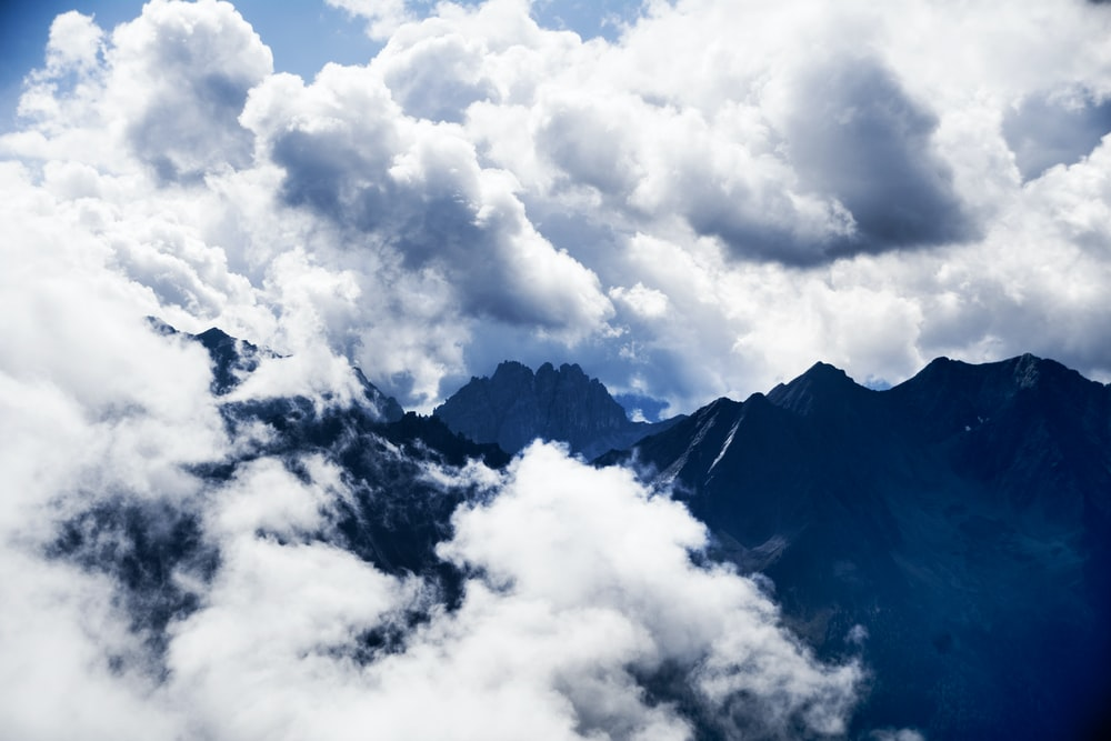 silhouette of mountain covered with white clouds during daytime