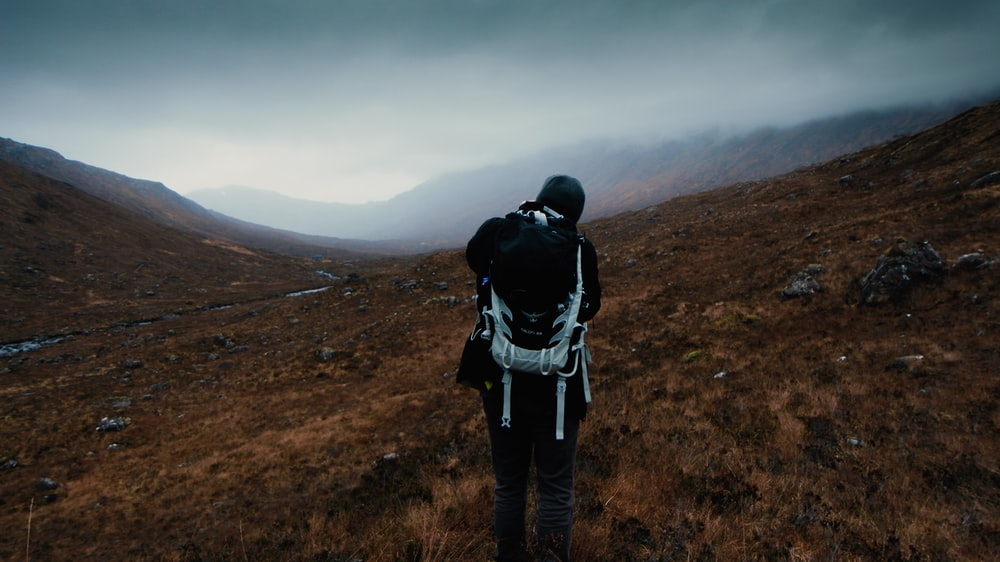 man carrying hiking bag standing under cloudy sky