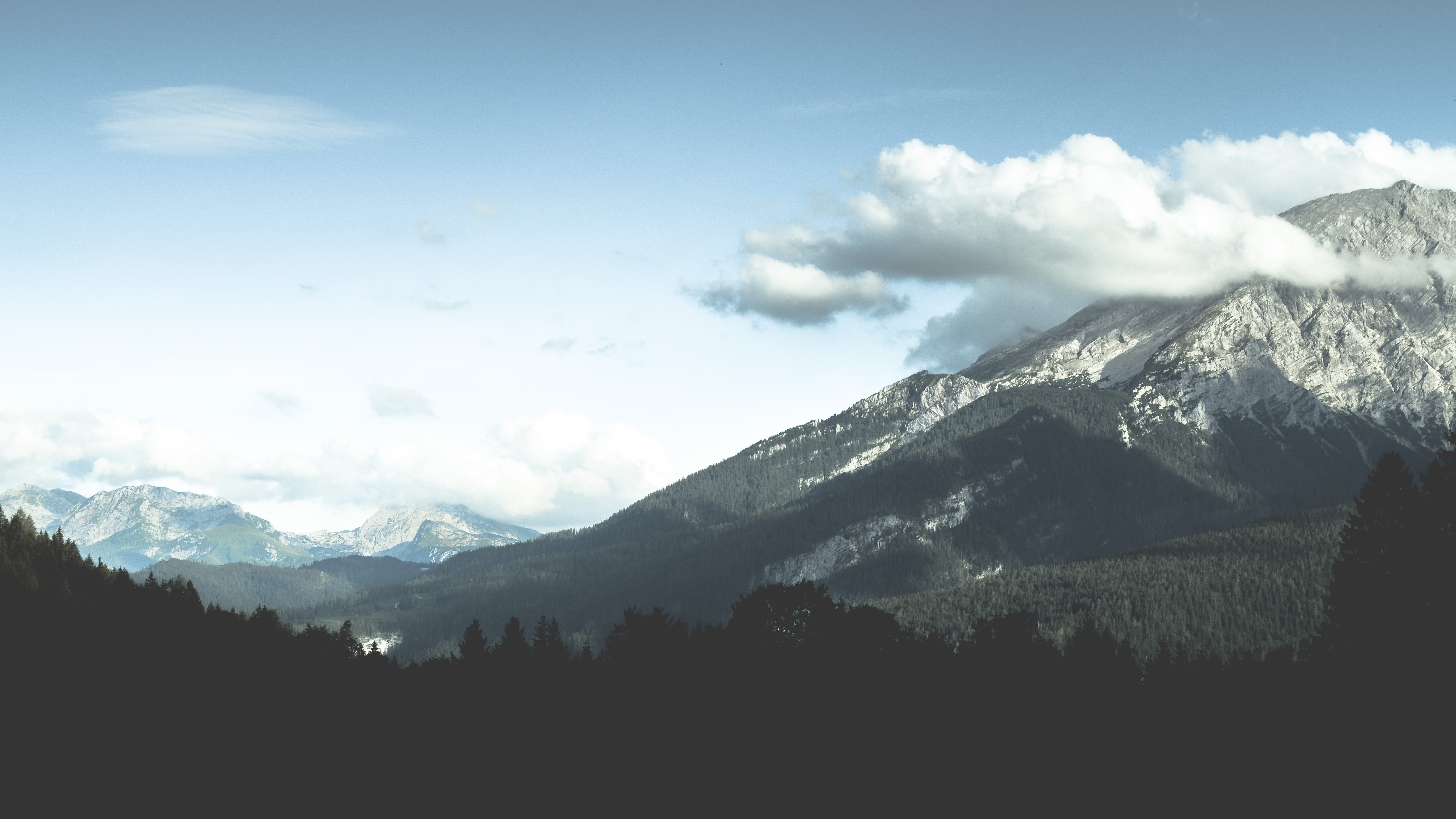 Clouds over wooded mountains in Hintersee
