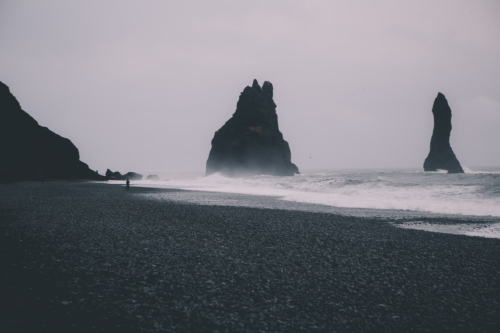 grayscale photo of beach with waves during daytime