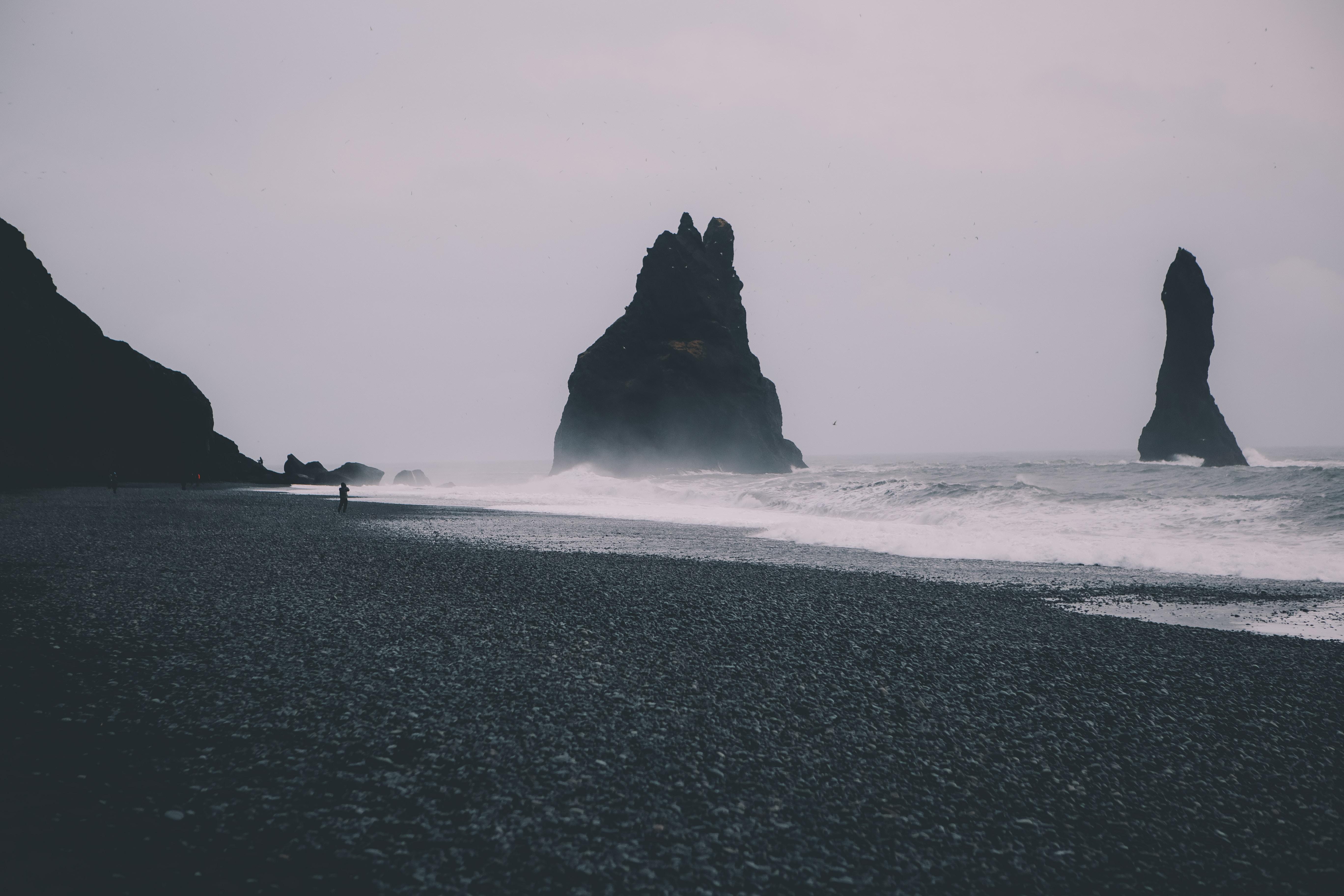Man standing on a black sand beach on an overcast day