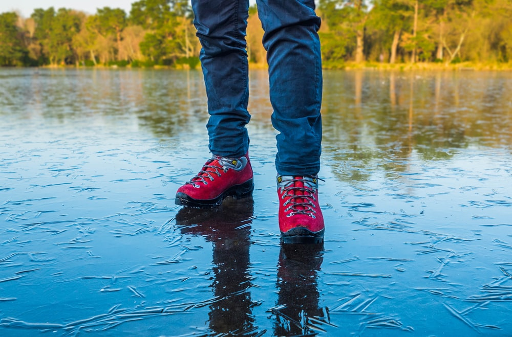 person wearing shoes standing on wet ground
