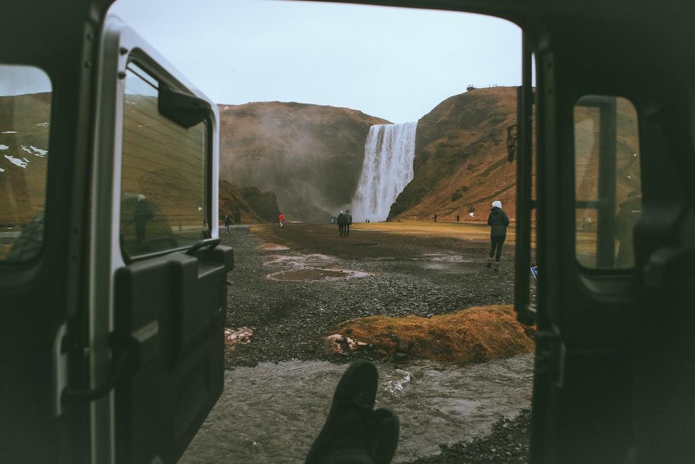 people standing around waterfall