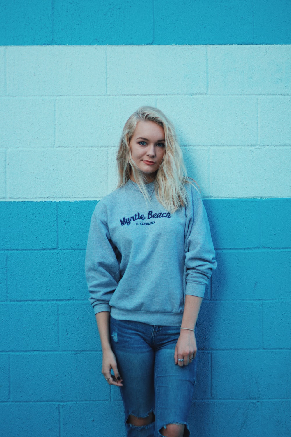 woman in teal sweater and blue jeans