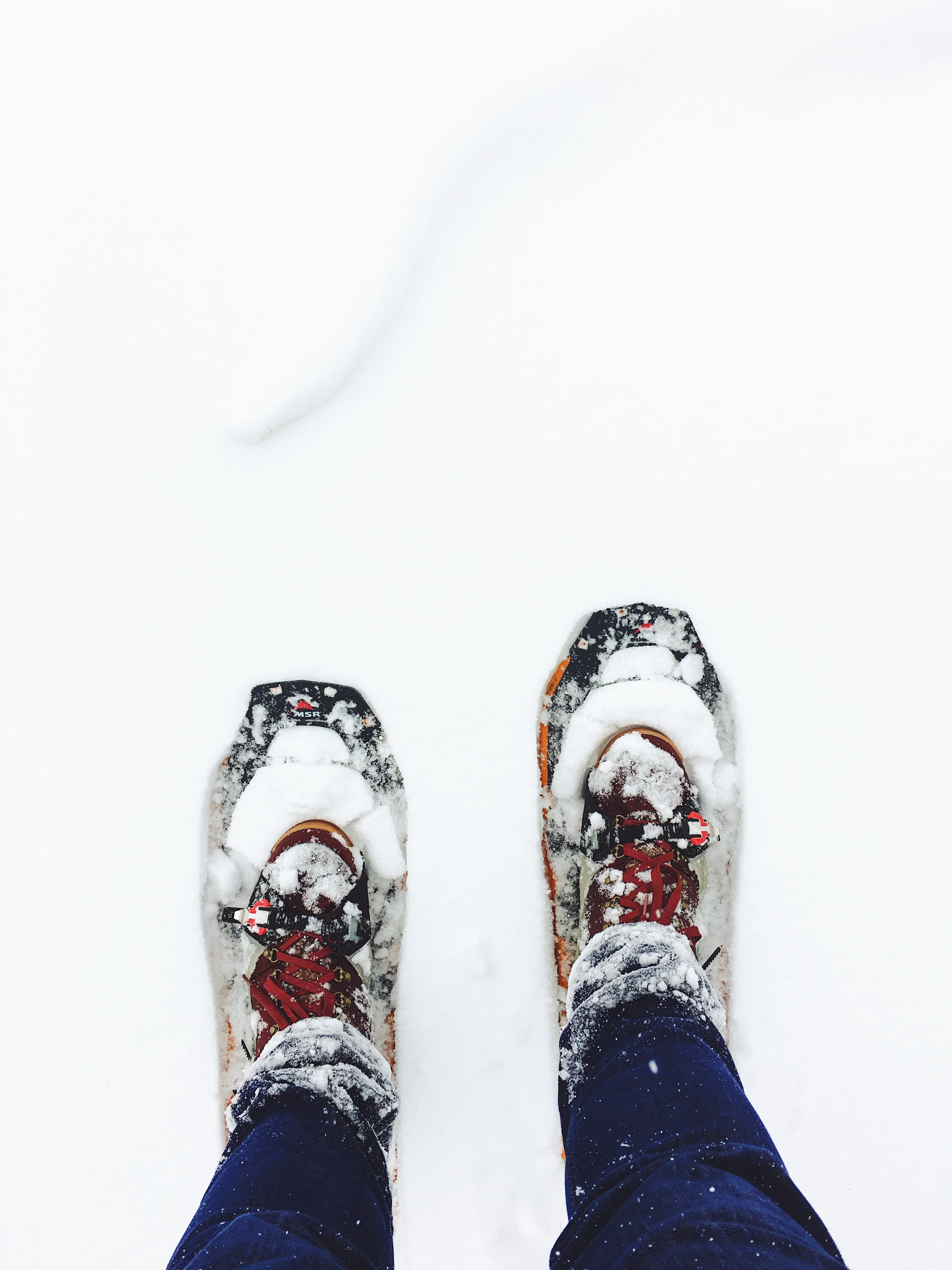 person wearing blue jeans standing on snow