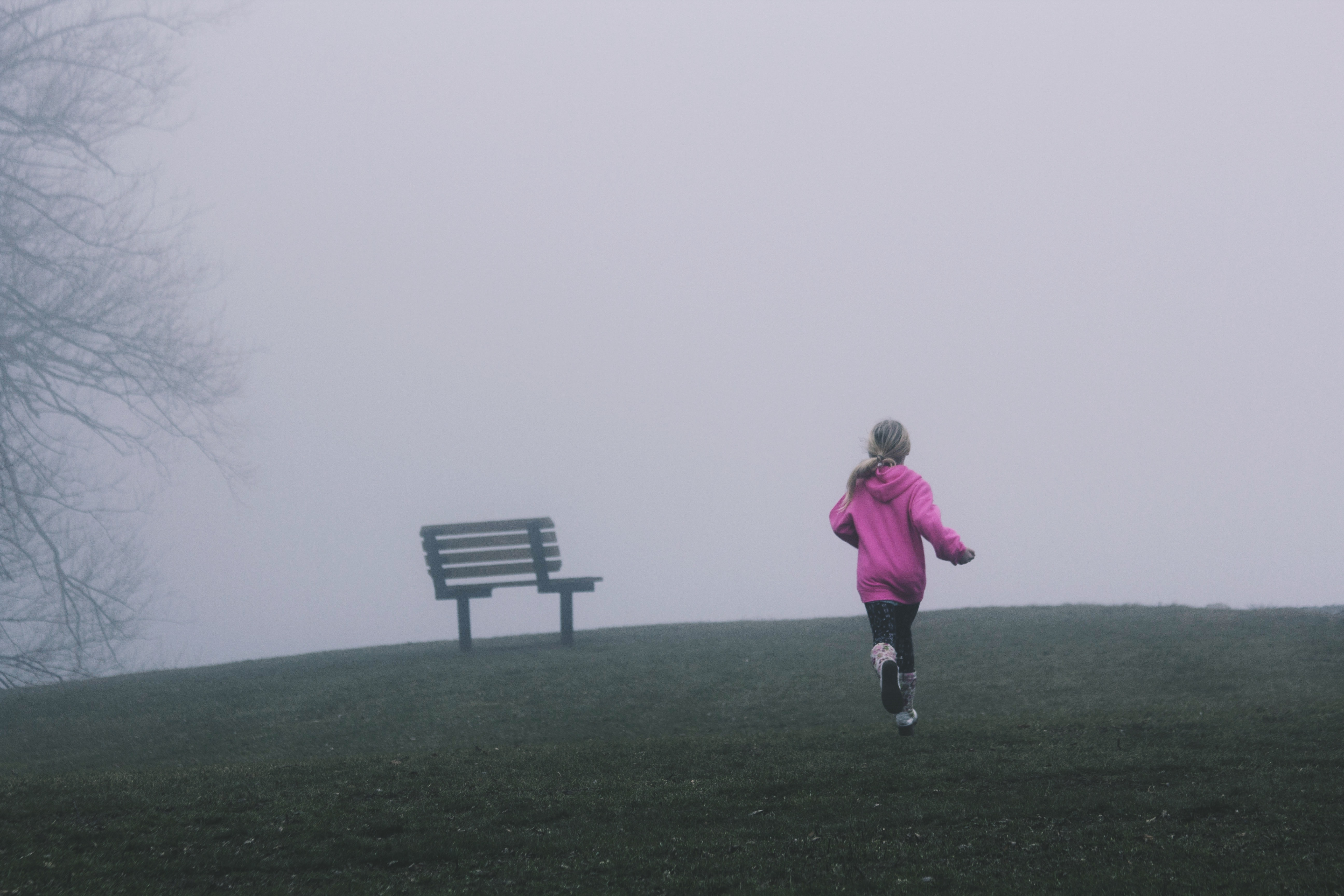 Girl runs towards a bench in a cold and foggy park
