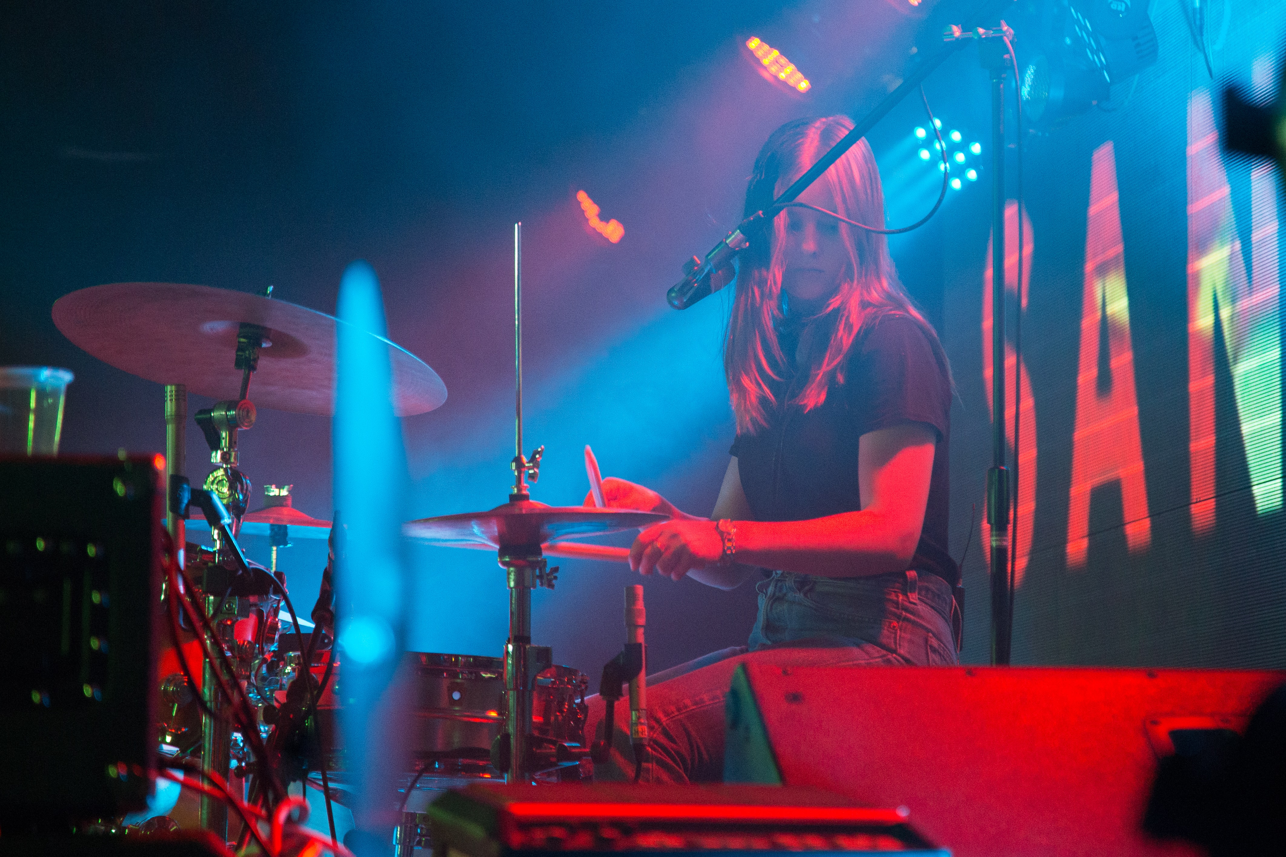 Woman plays drums in blue and red stage light during a show