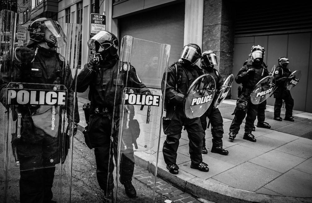 policemen holding clear fiber glass shield