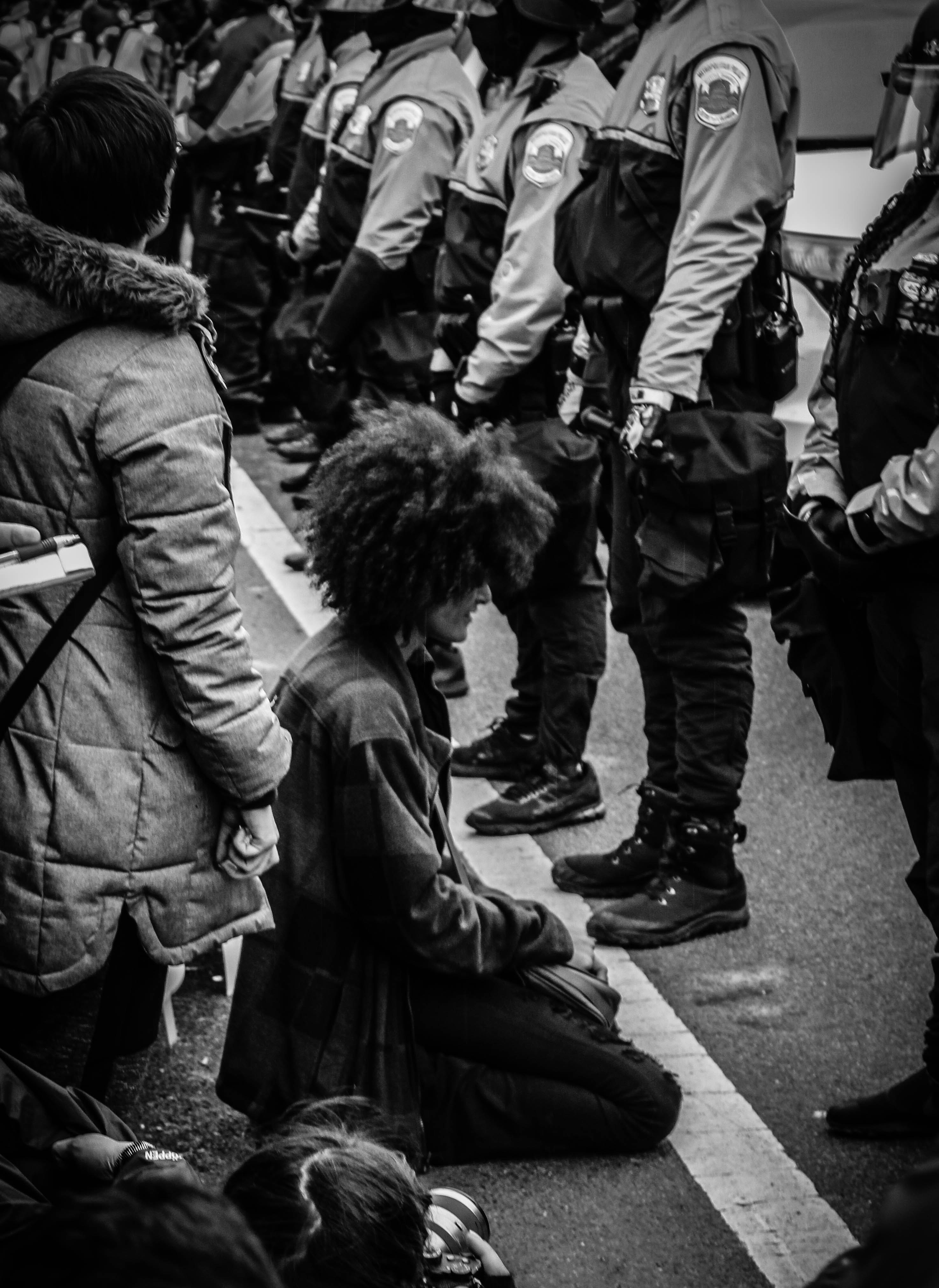 person kneeling before police officers
