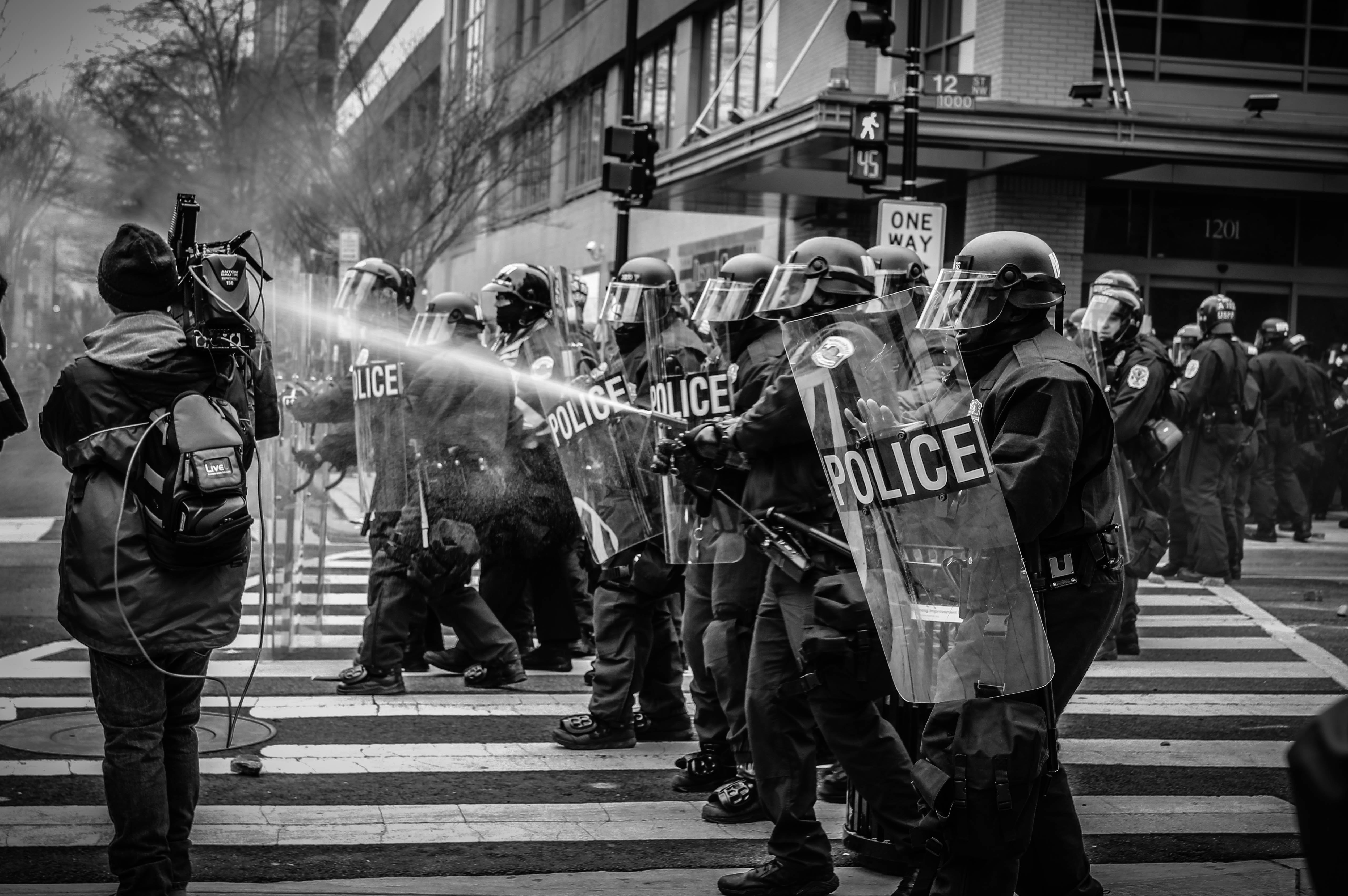 grayscale photo of police riot team on pedestrian lane
