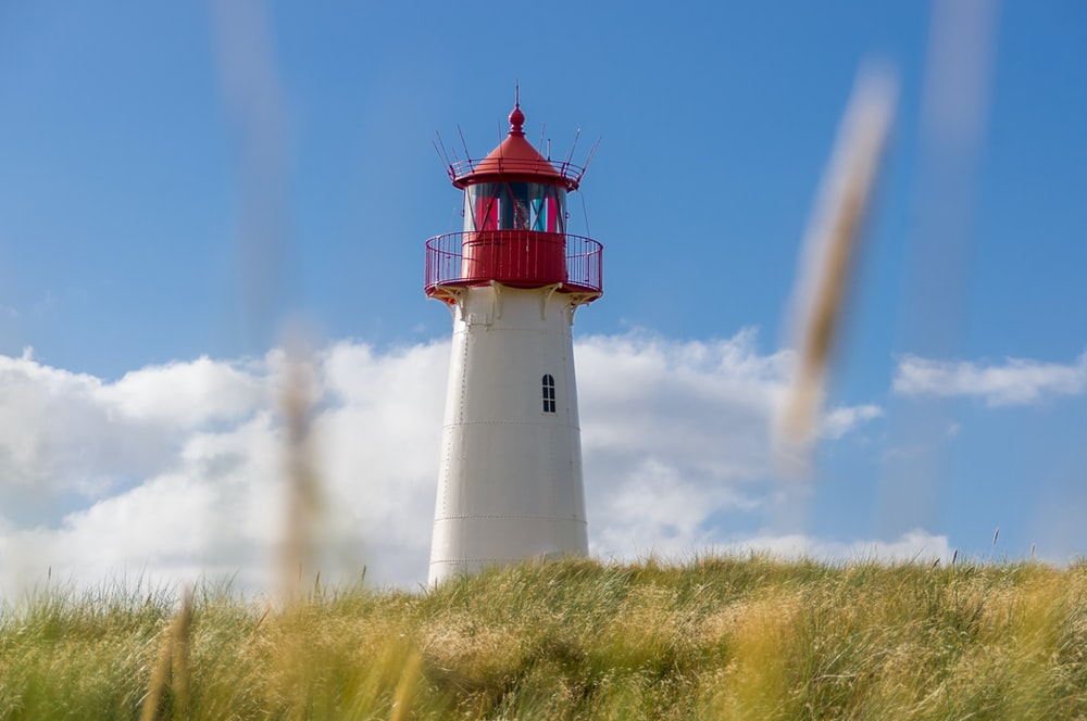white and red lighthouse under blue and white cloudy sky photo
