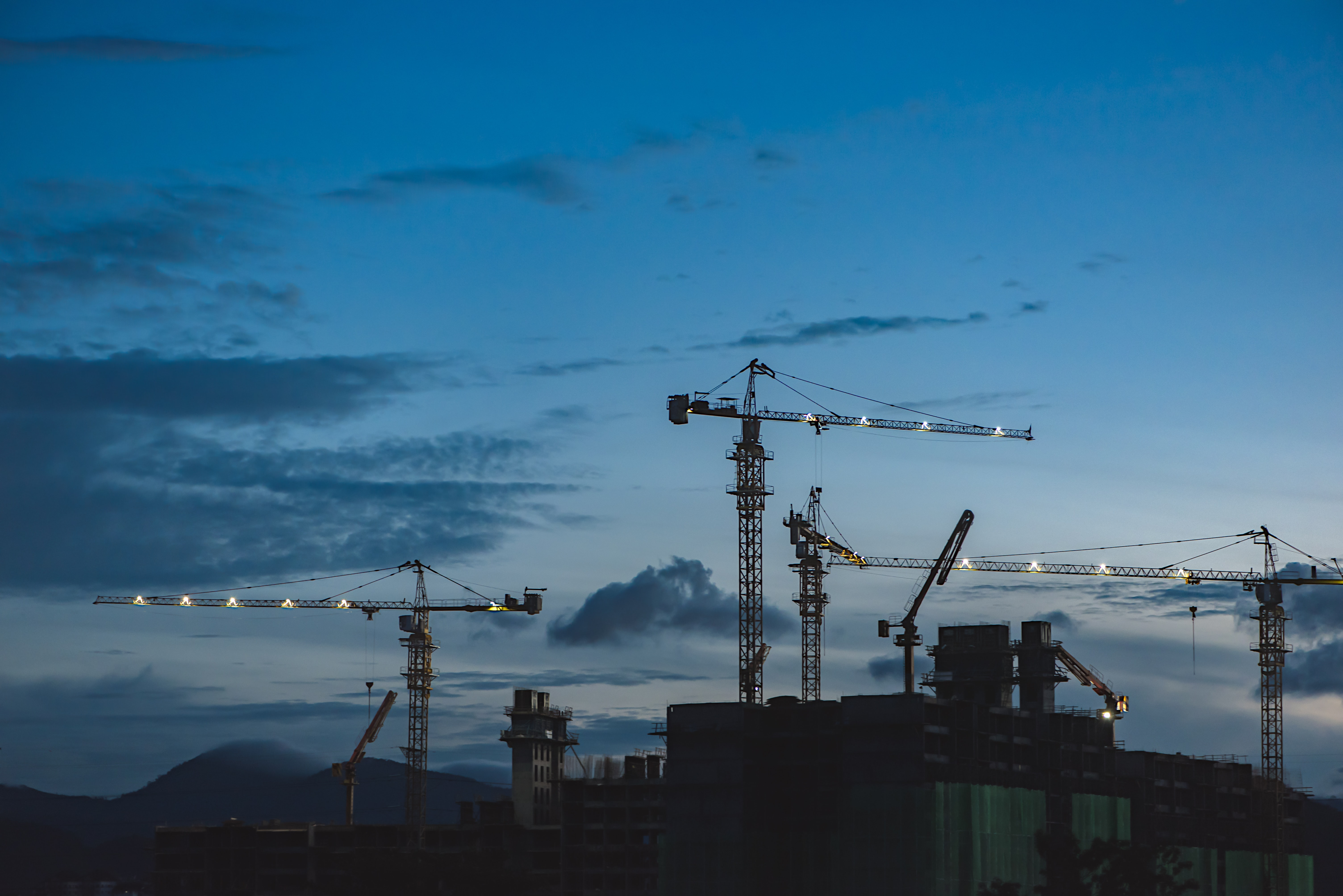 several cranes above the buildings
