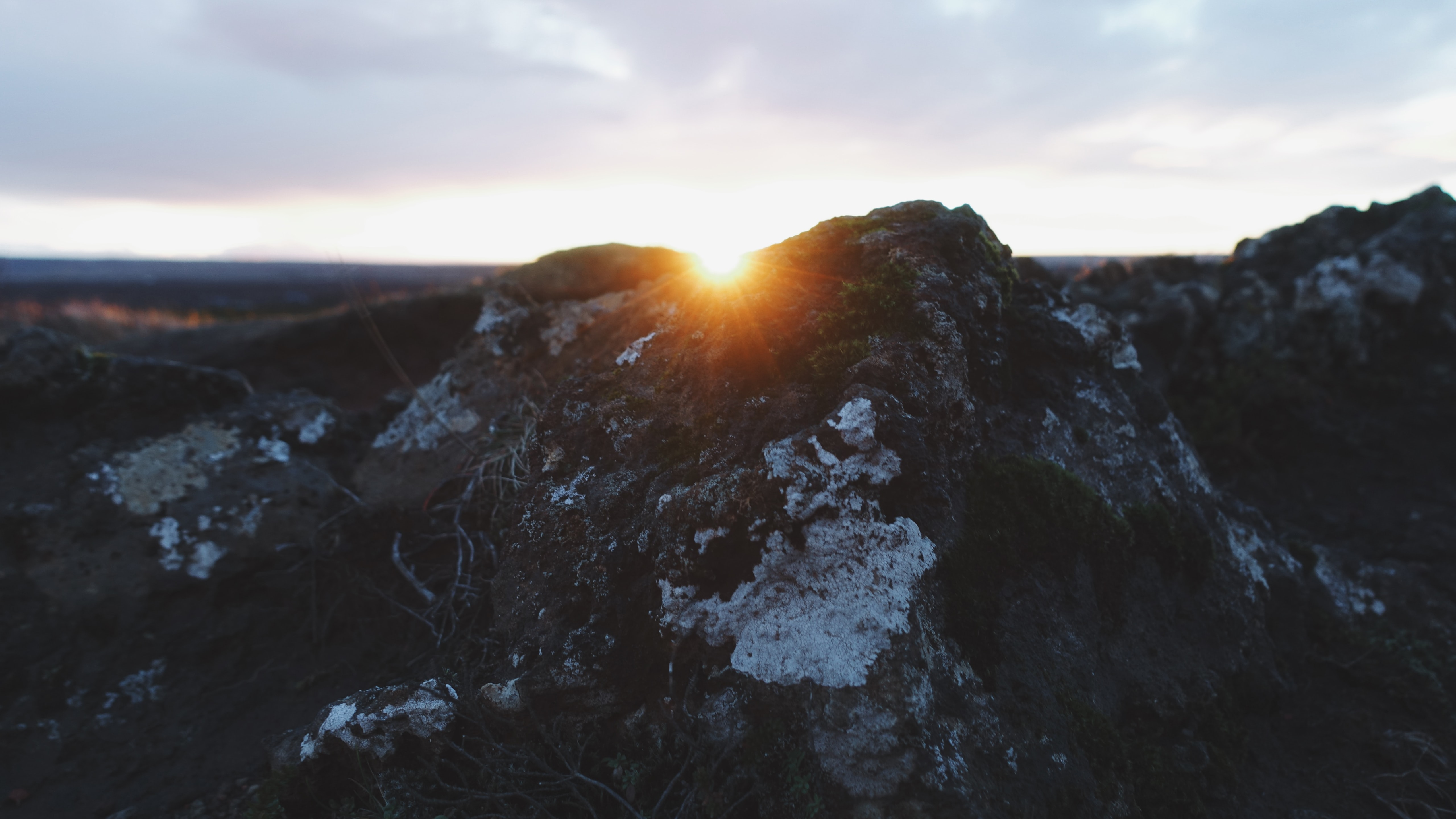 Snow sits on mountains as the sun sets below the peak at Kerið.
