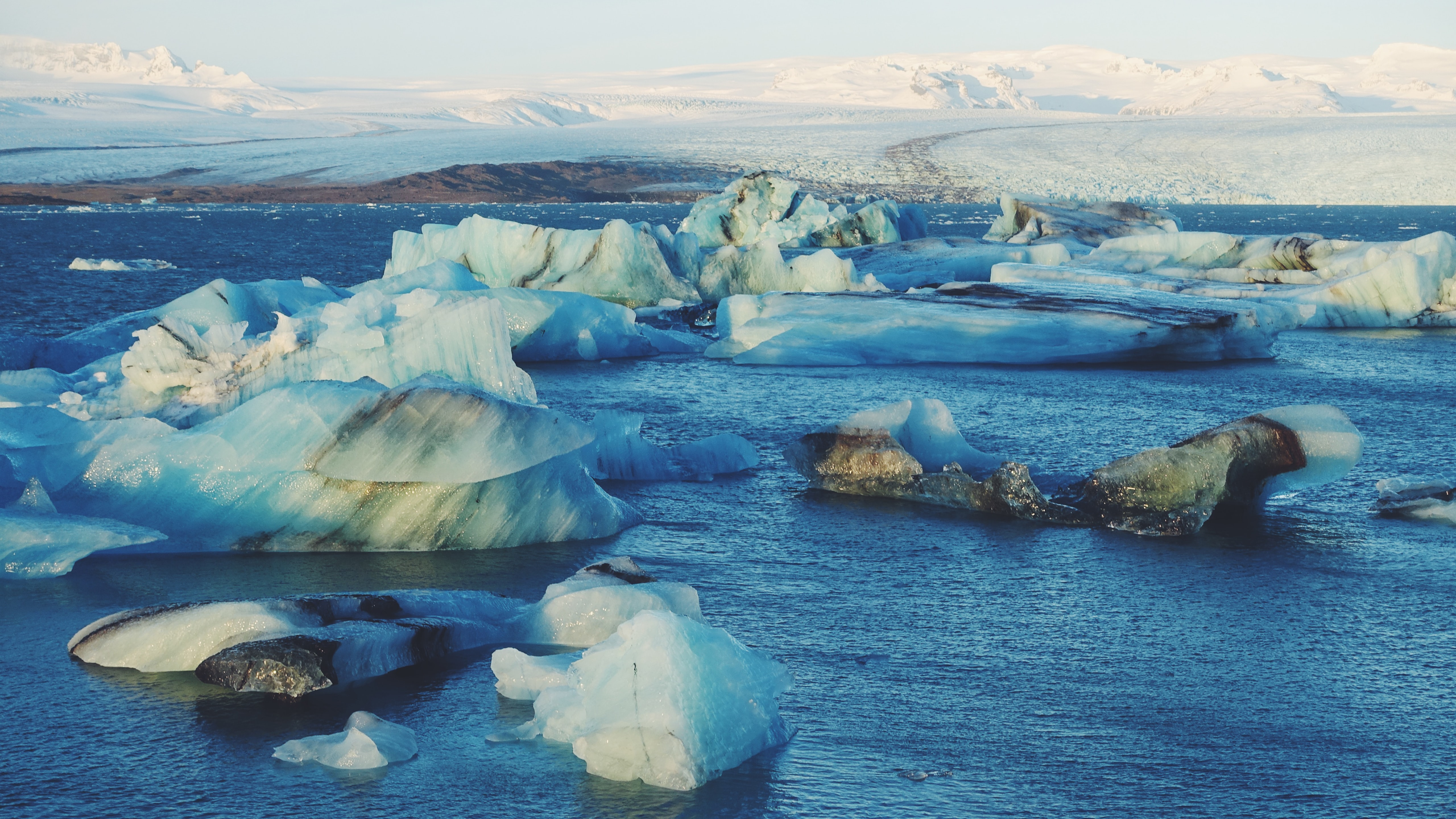 Arctic glaciers in water with snow covered mountains in the distance