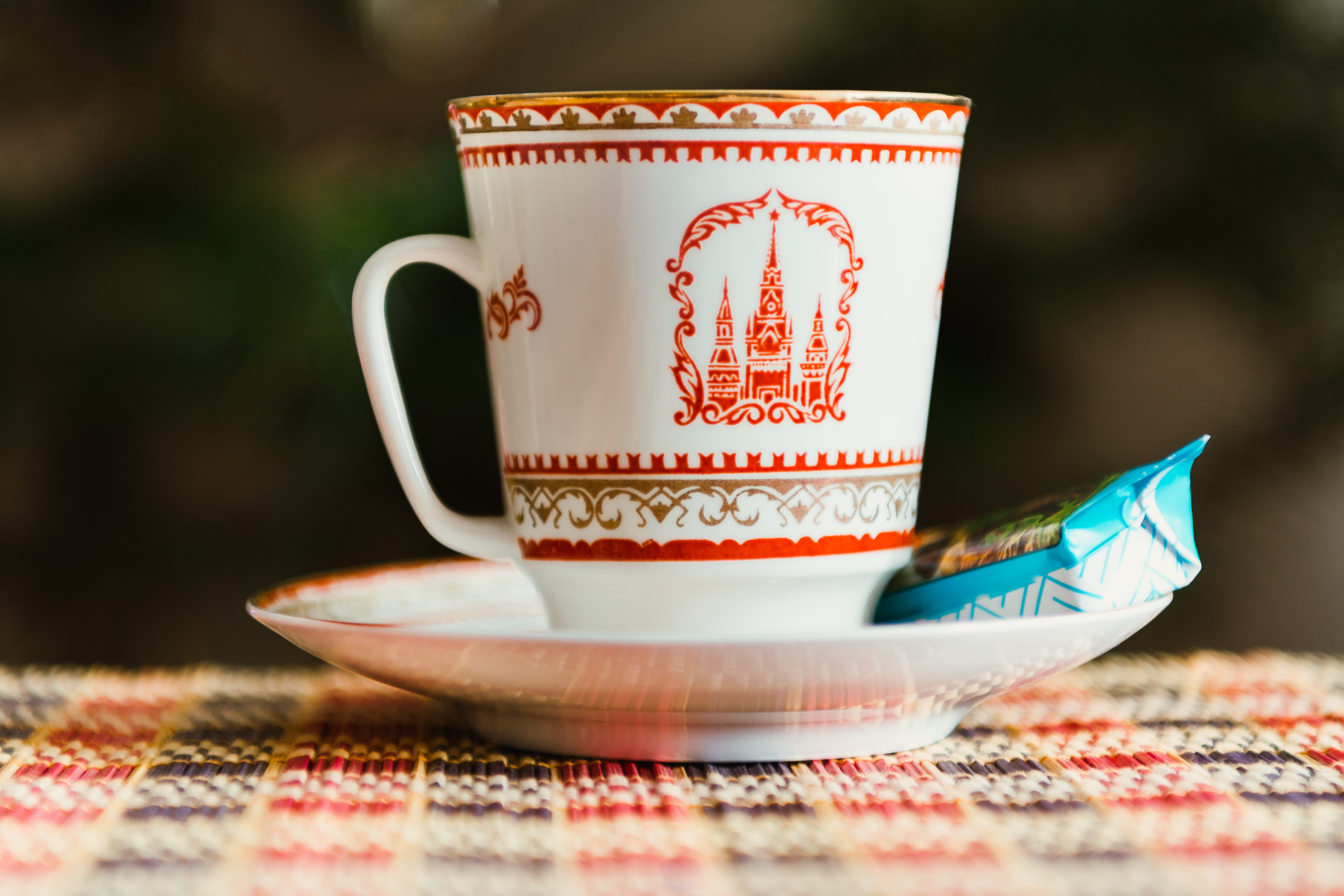 A ceramic cup with a castle on it sitting on a saucer with a biscuit in a wrapper