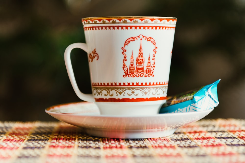 selective focus photography of white-and-red teacup on saucer with blue labeled food pack