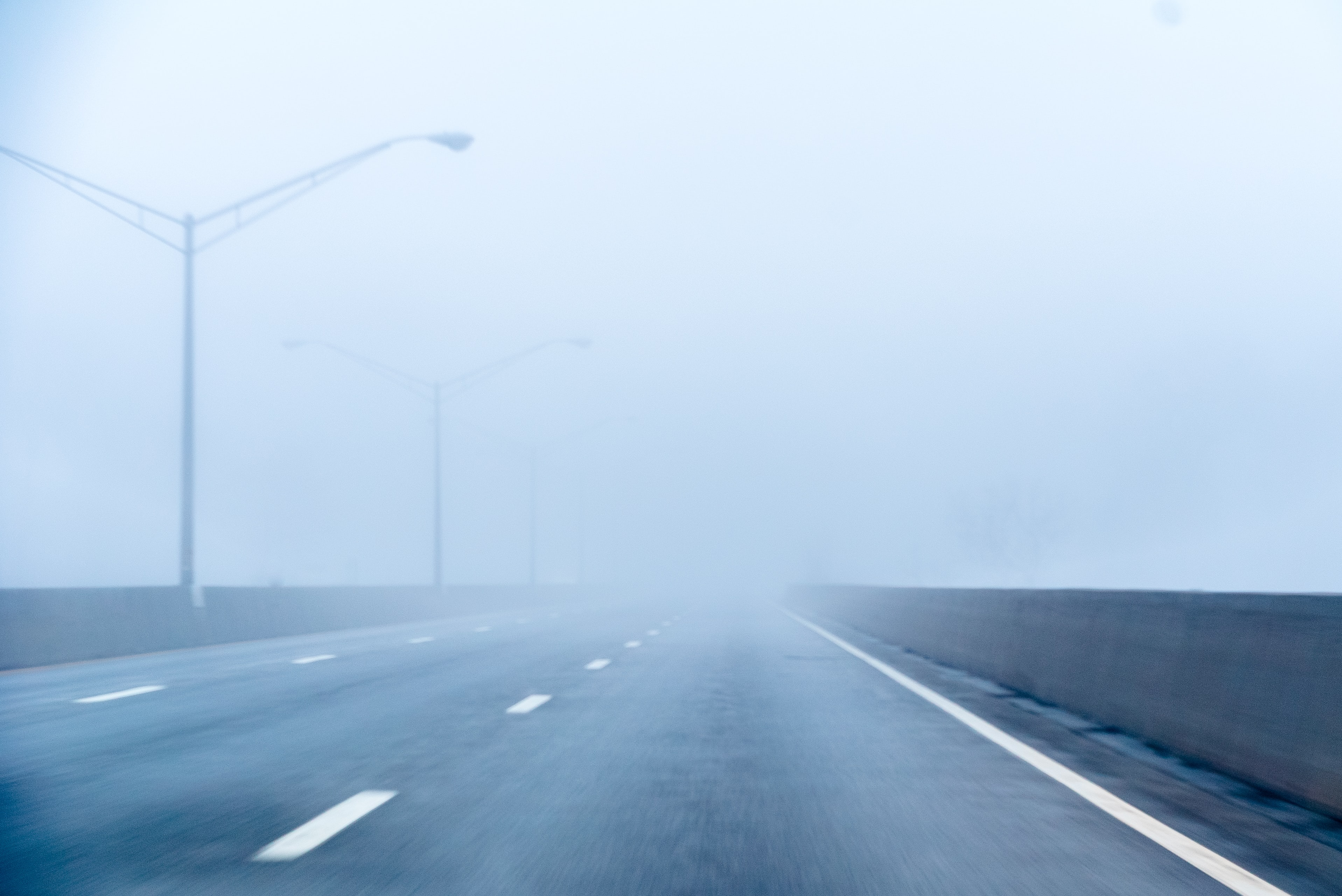Foggy empty highway with streetlights on a morning drive