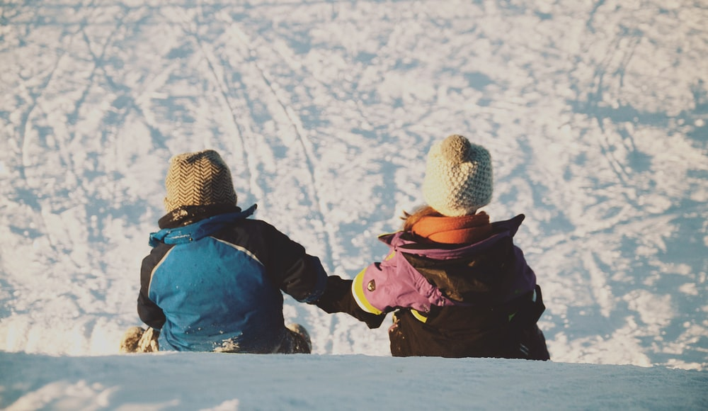 two people sitting on snow during daytime