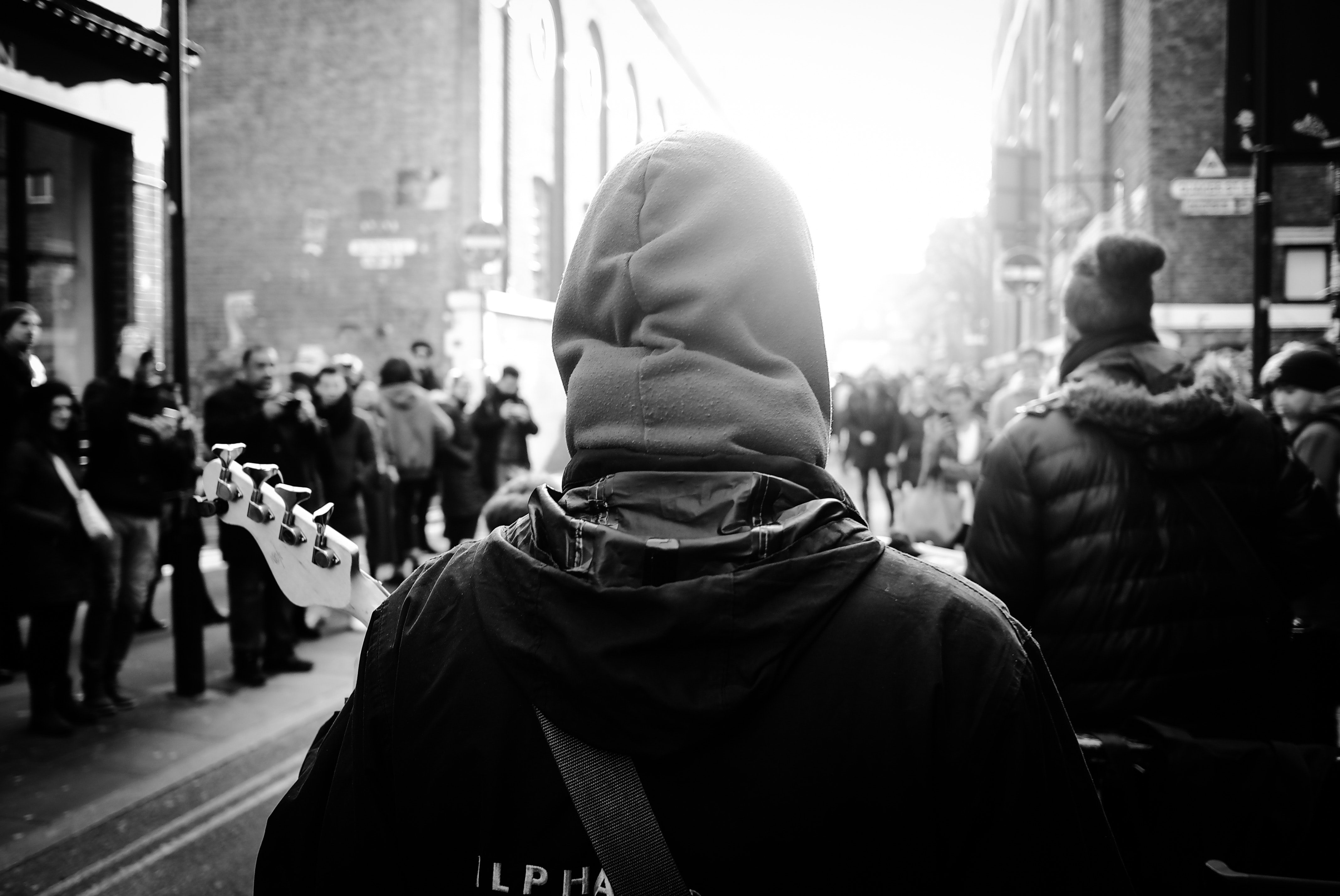 A black and white shot from behind civilians wearing hooded jackets and walking through London