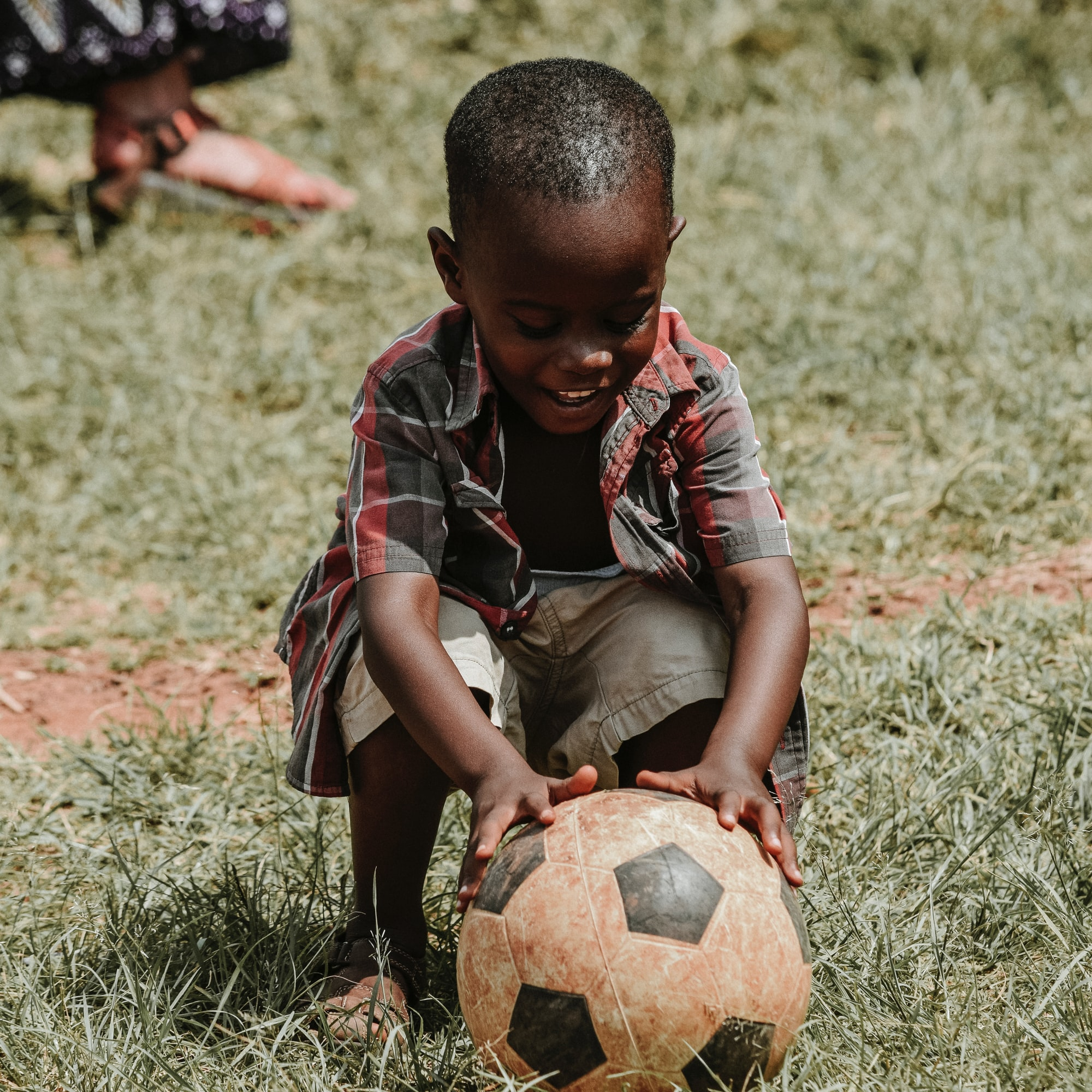 Child smiling with a soccer ball