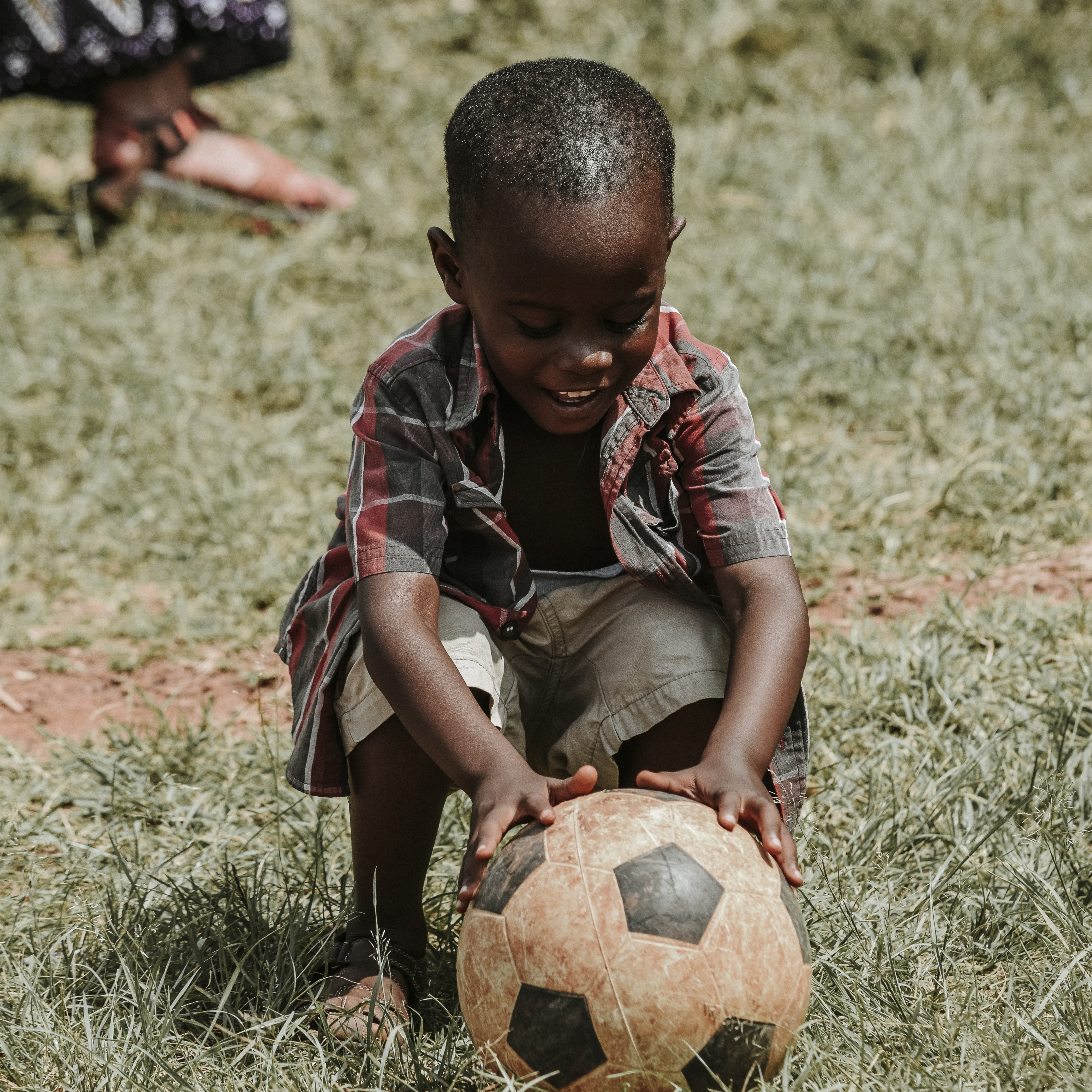 Child smiling and touching the dirty soccer ball  in the field with hands