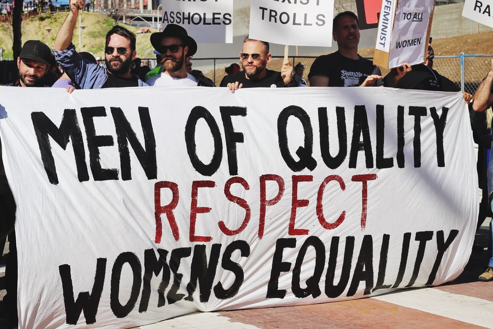 feminists holding white, black, and red Men of quality respect womens equality banner on road at womens march