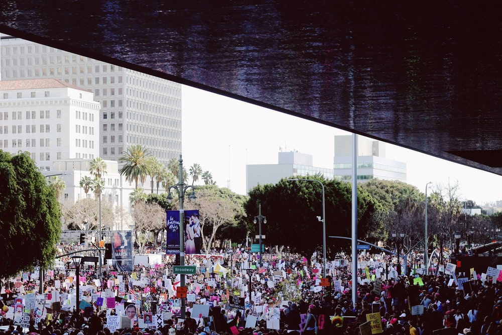 crowd of people near concrete buildings during daytime