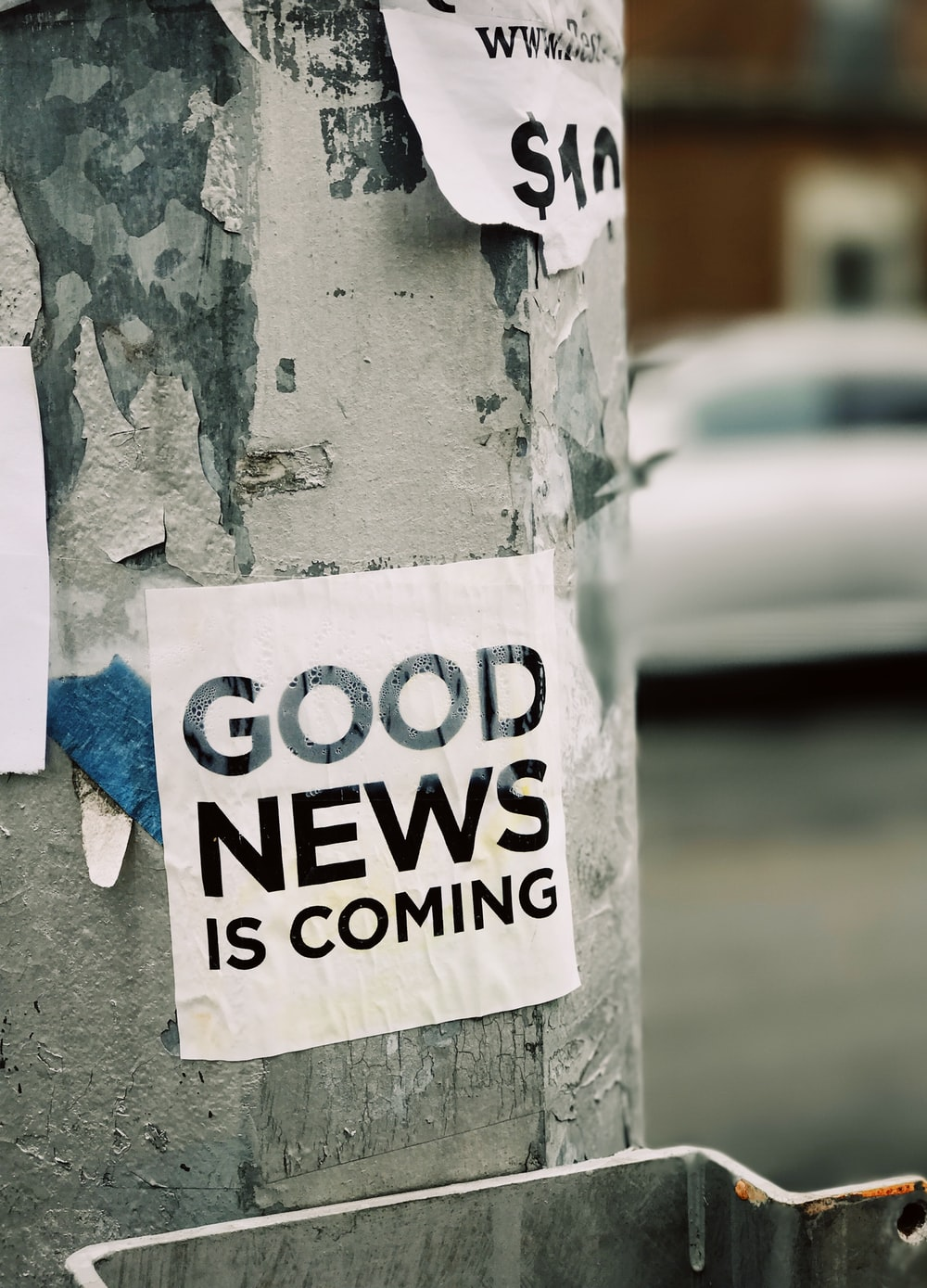 white Good News Is Coming paper on wall