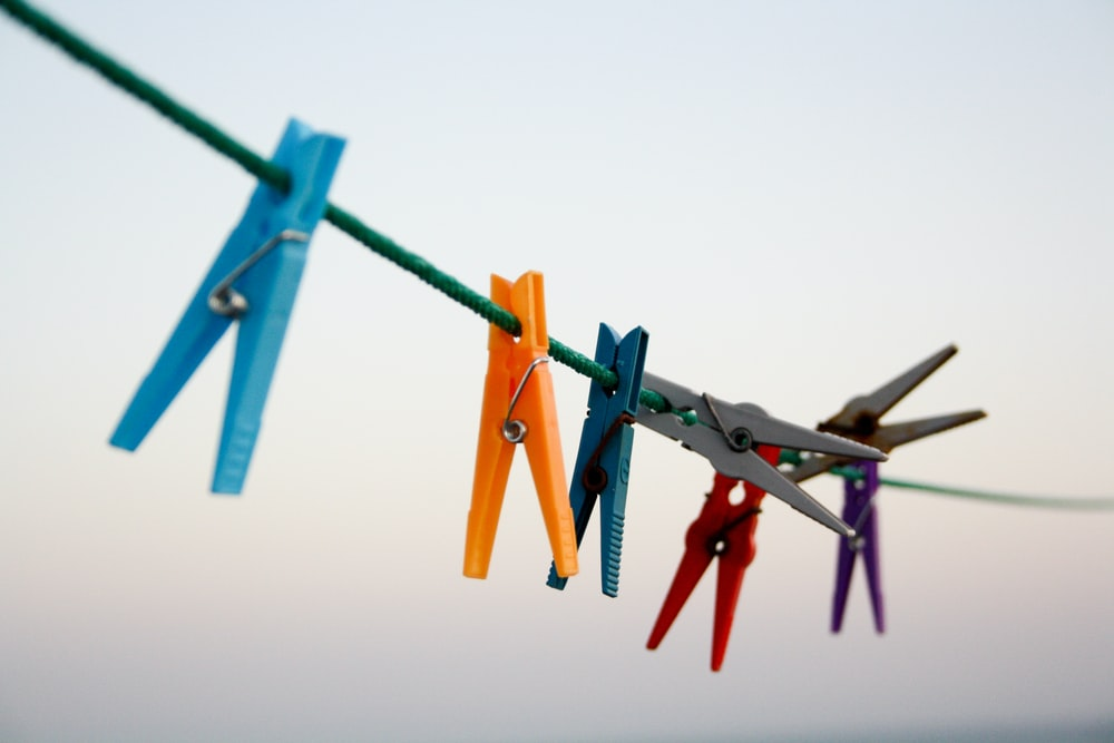 seven assorted-color clothes pegs hanging on rope \
