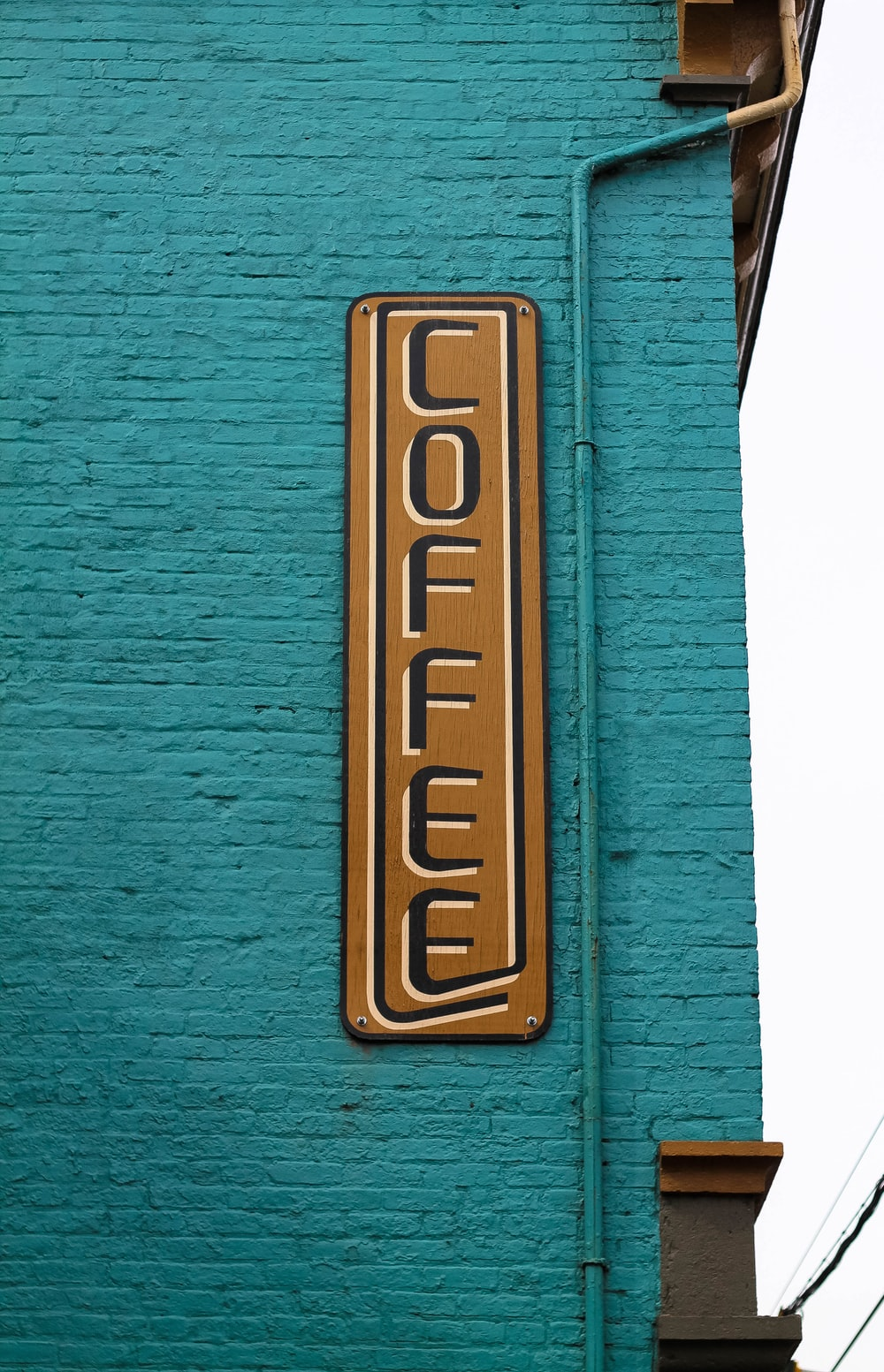 brown and black wooden coffee sign board on blue brick wall at daytime