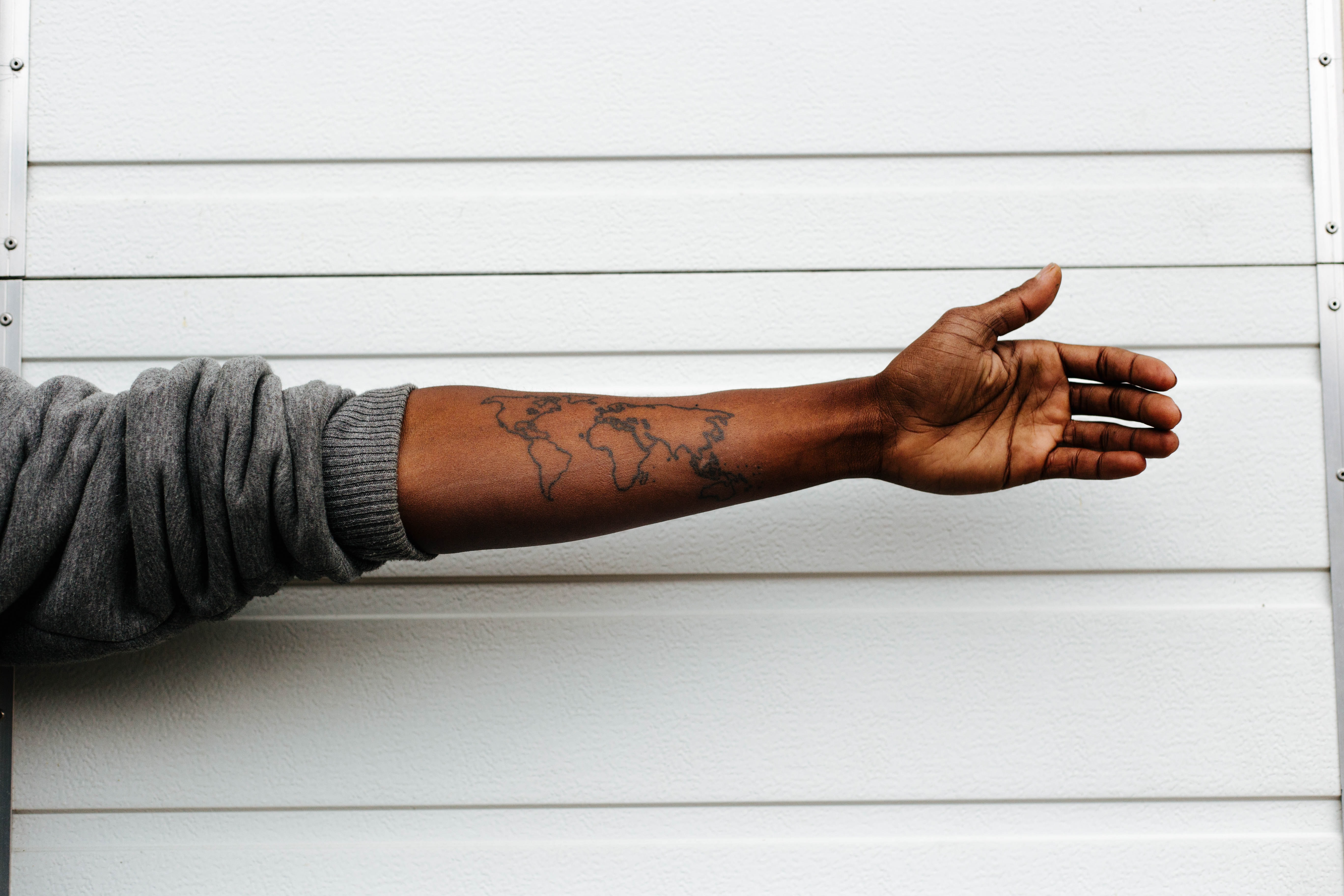man raising hand with map arm tattoo behind white painted wall